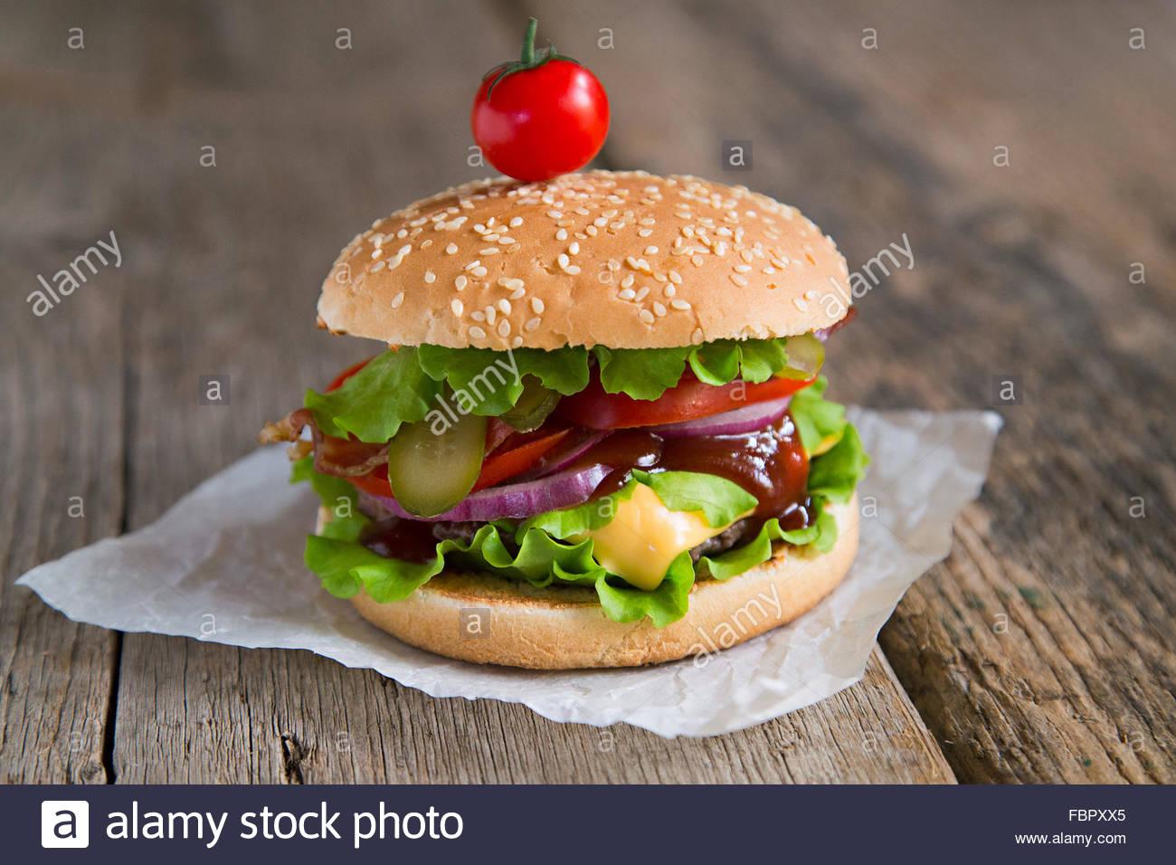 Burger mit Speck, Tomaten, Zwiebeln, Barbecue-sauce Stockbild