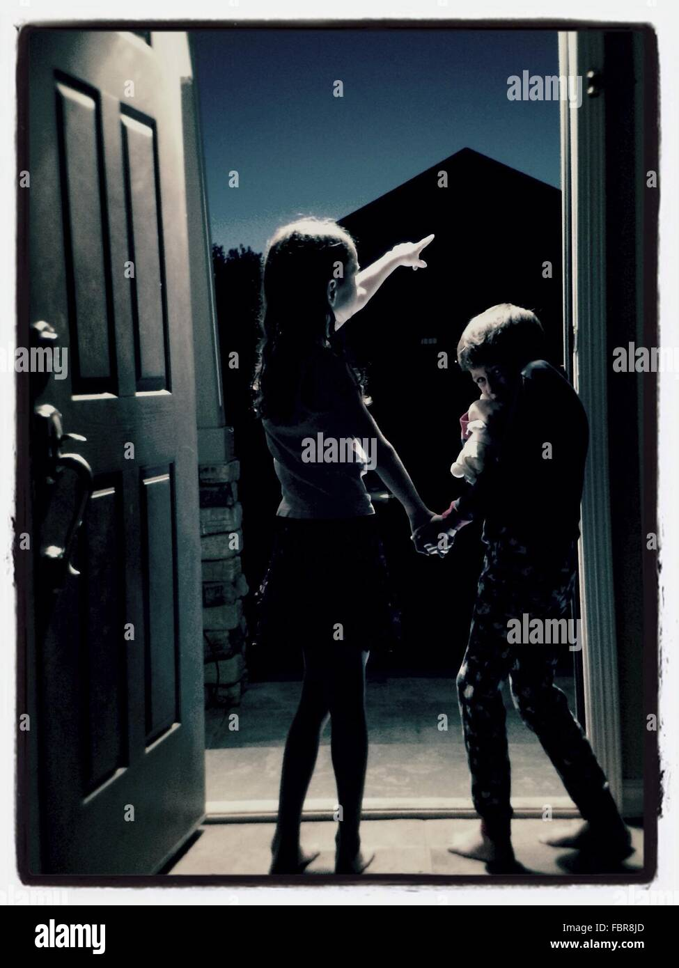 Geschwister, die nachts auf Tür stehen Stockbild