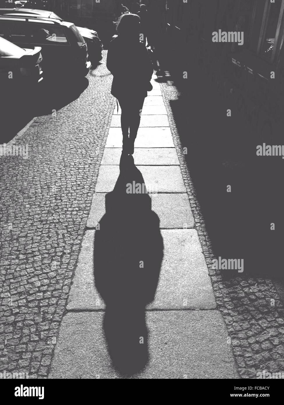 Rückansicht der Frau zu Fuß auf Bürgersteig an sonnigen Tag Stockbild