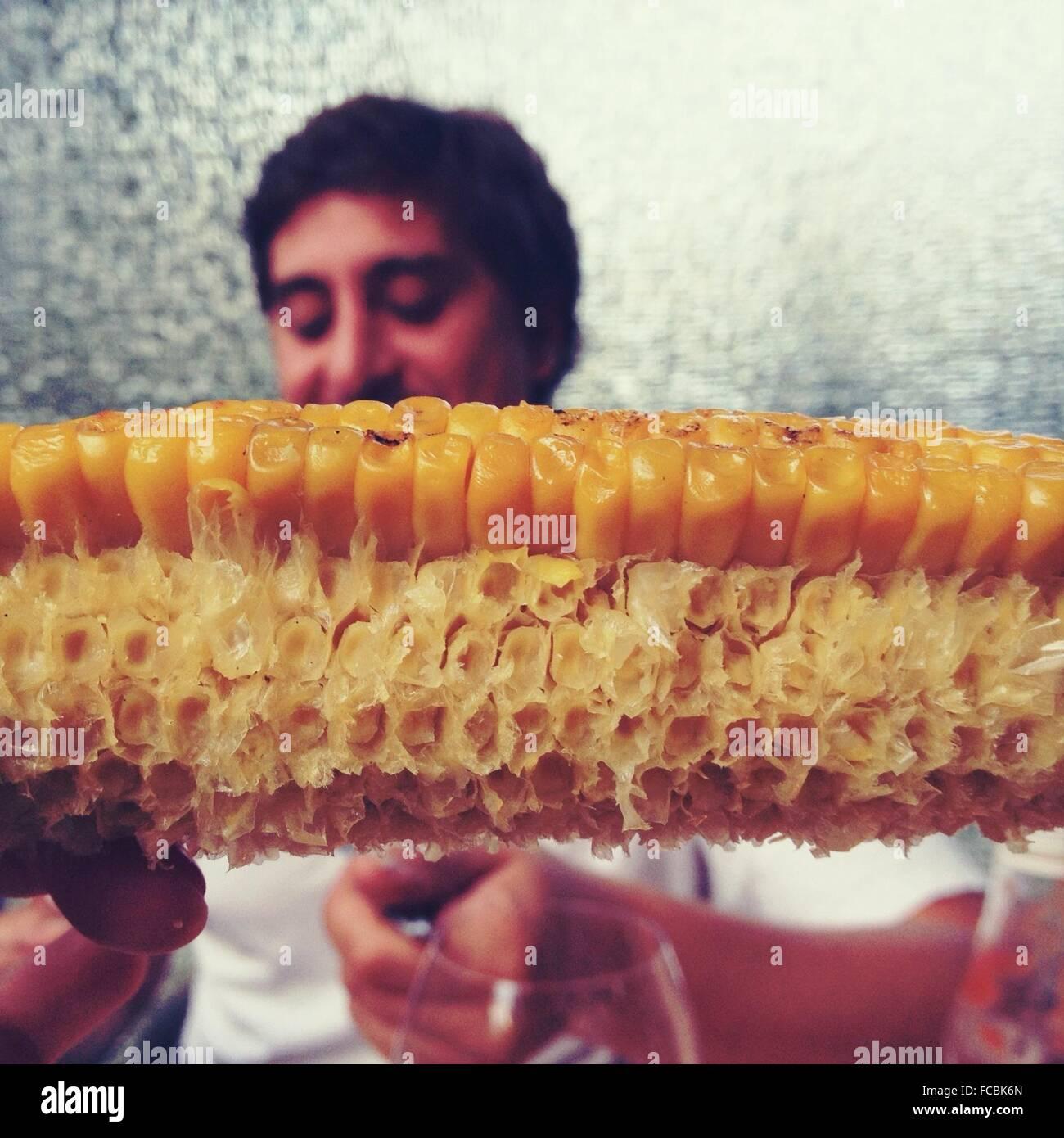Detail des gegessenen Mais mit Mann im Hintergrund Stockbild