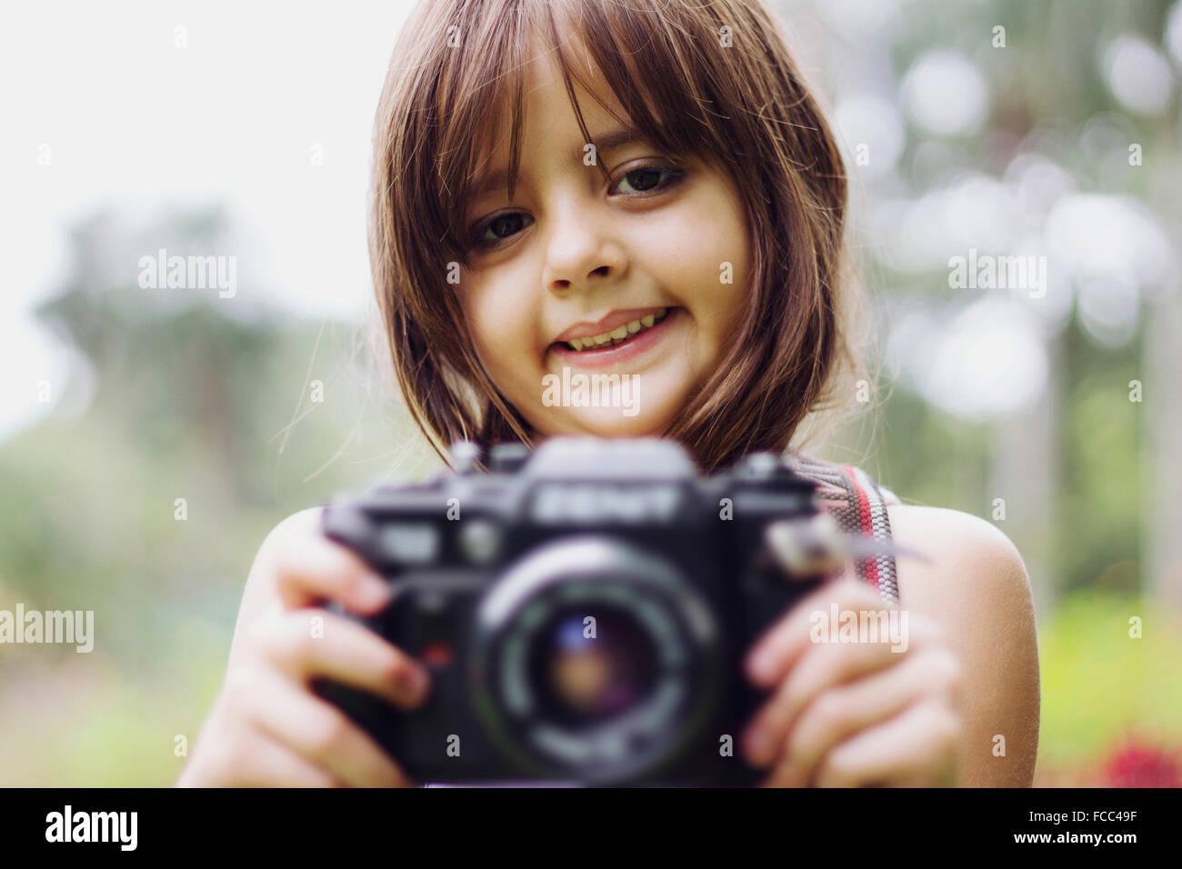 Porträt eines lächelnden Mädchens Kamera im Freien halten Stockbild