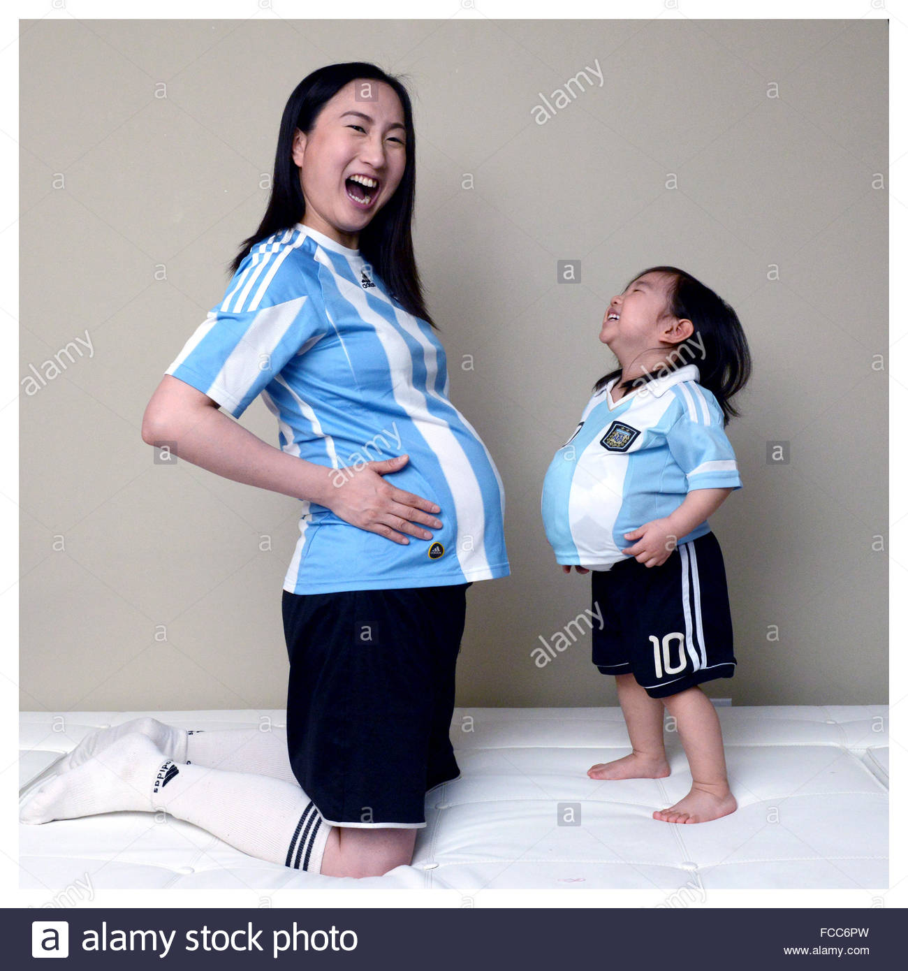 Glückliche Tochter schwanger Mutter zu Hause zu imitieren Stockbild