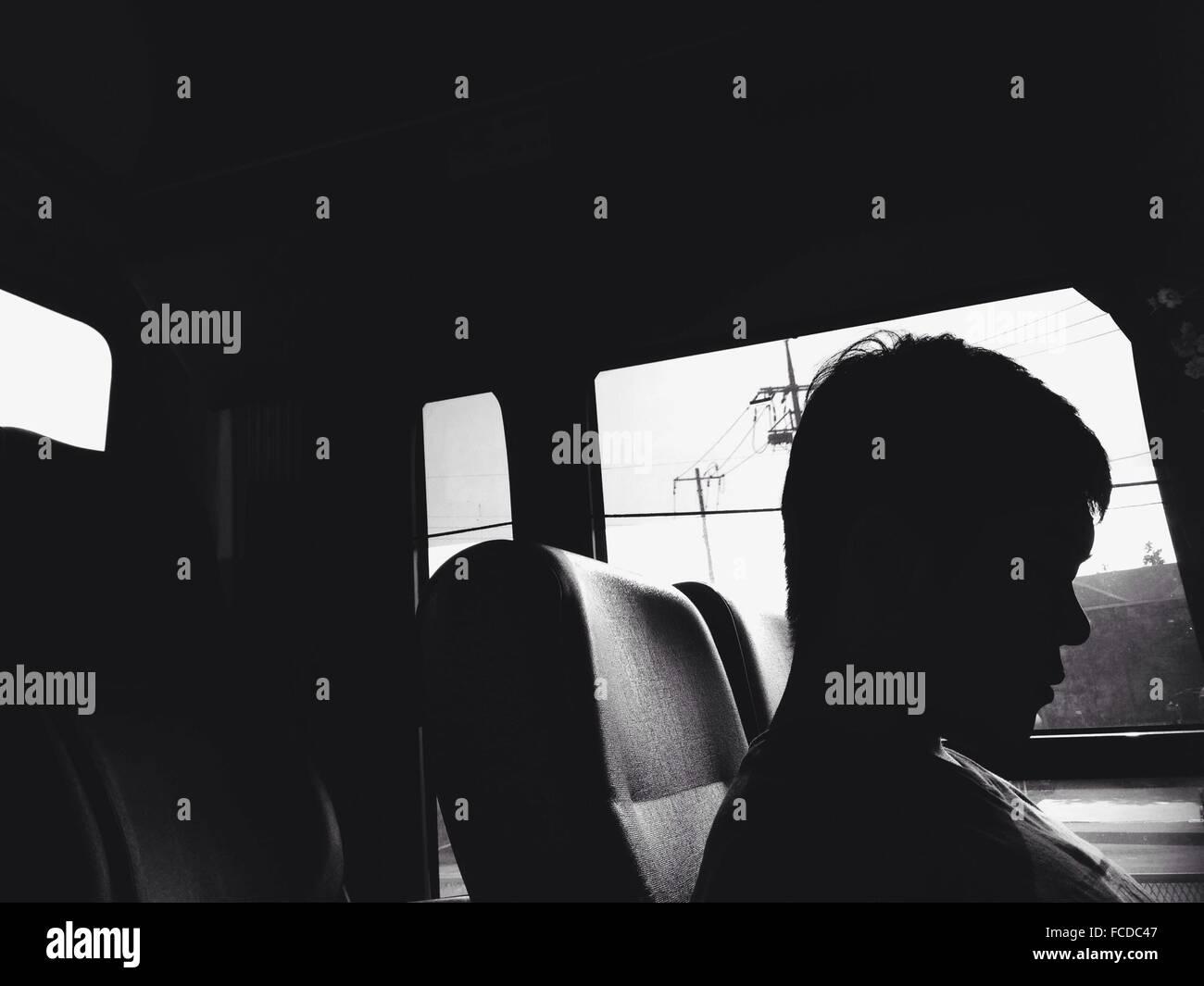 Silhouette der Mann sitzt im Auto Stockbild