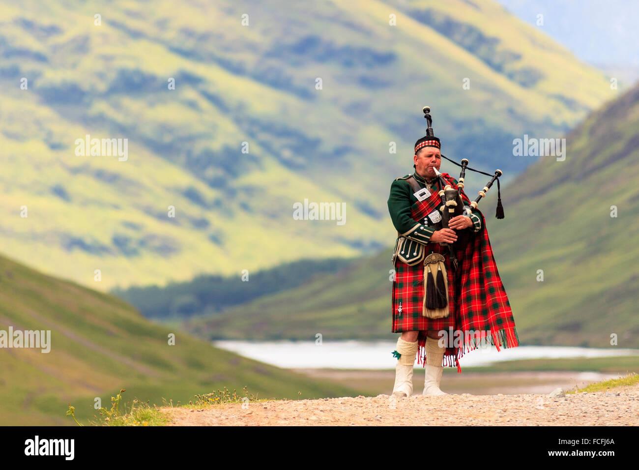 Dudelsack vor Loch Achtriochtan und steile Hügel im Hintergrund in Glencoe, Highlands, Schottland, UK Modell Stockbild