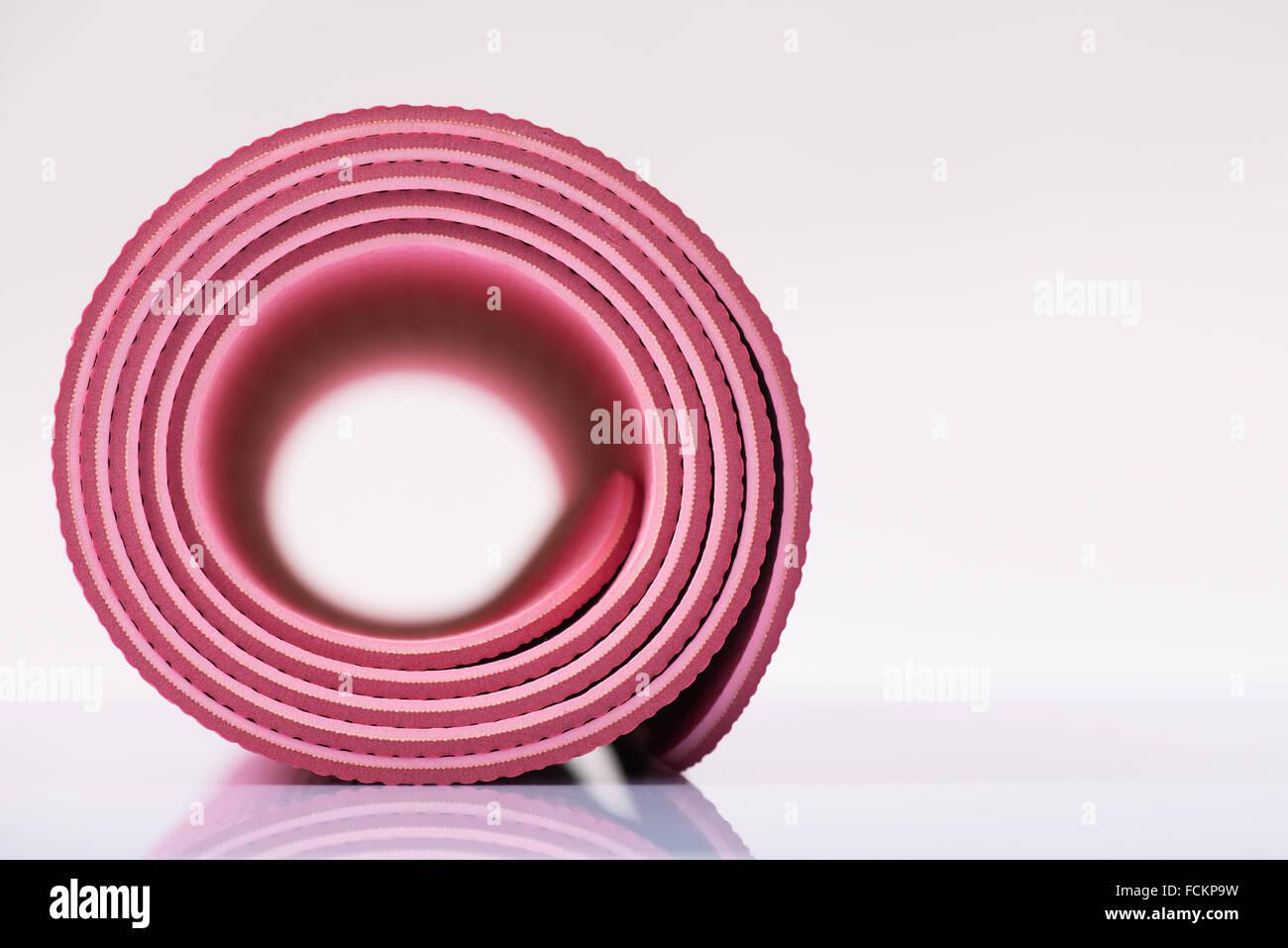 Yoga-Matte auf reflektierenden Oberfläche aufgerollt. Stockbild
