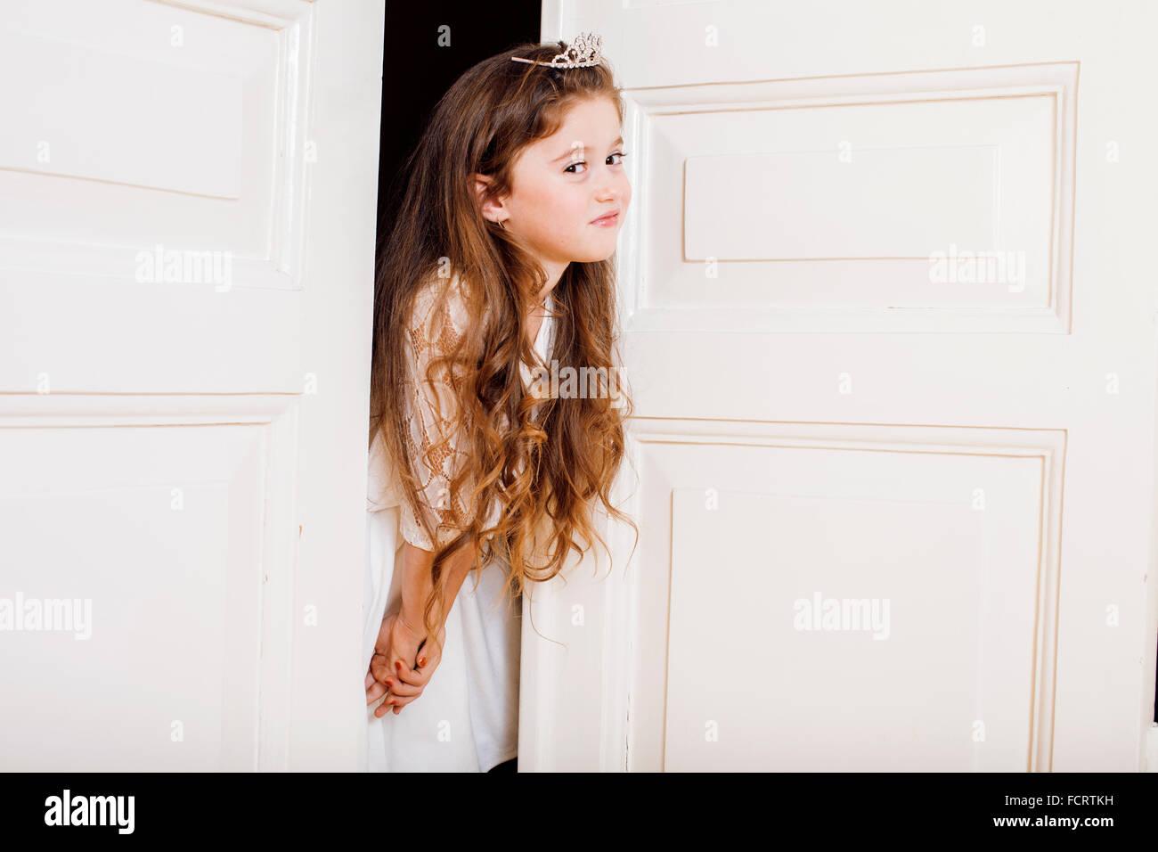 kleine süße Mädchen zu Hause, die Tür gut gekleidet in weißem Kleid, entzückende Fee Stockbild