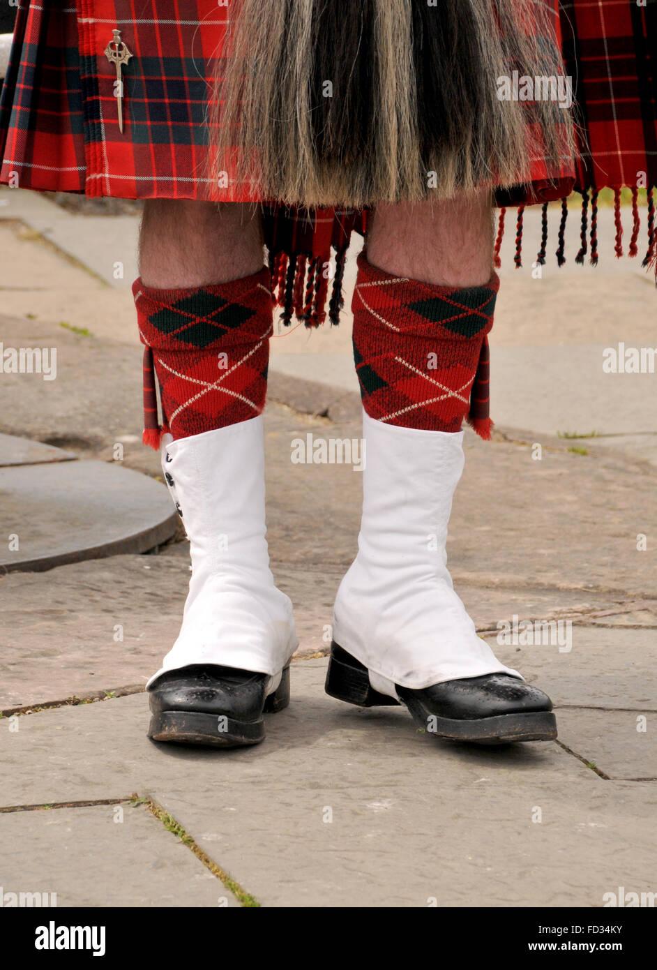 Beine und Schuhe von einem ständigen schottischen Mann gekleidet in einen roten aufgegebenes Tartan Kilt. Stockbild