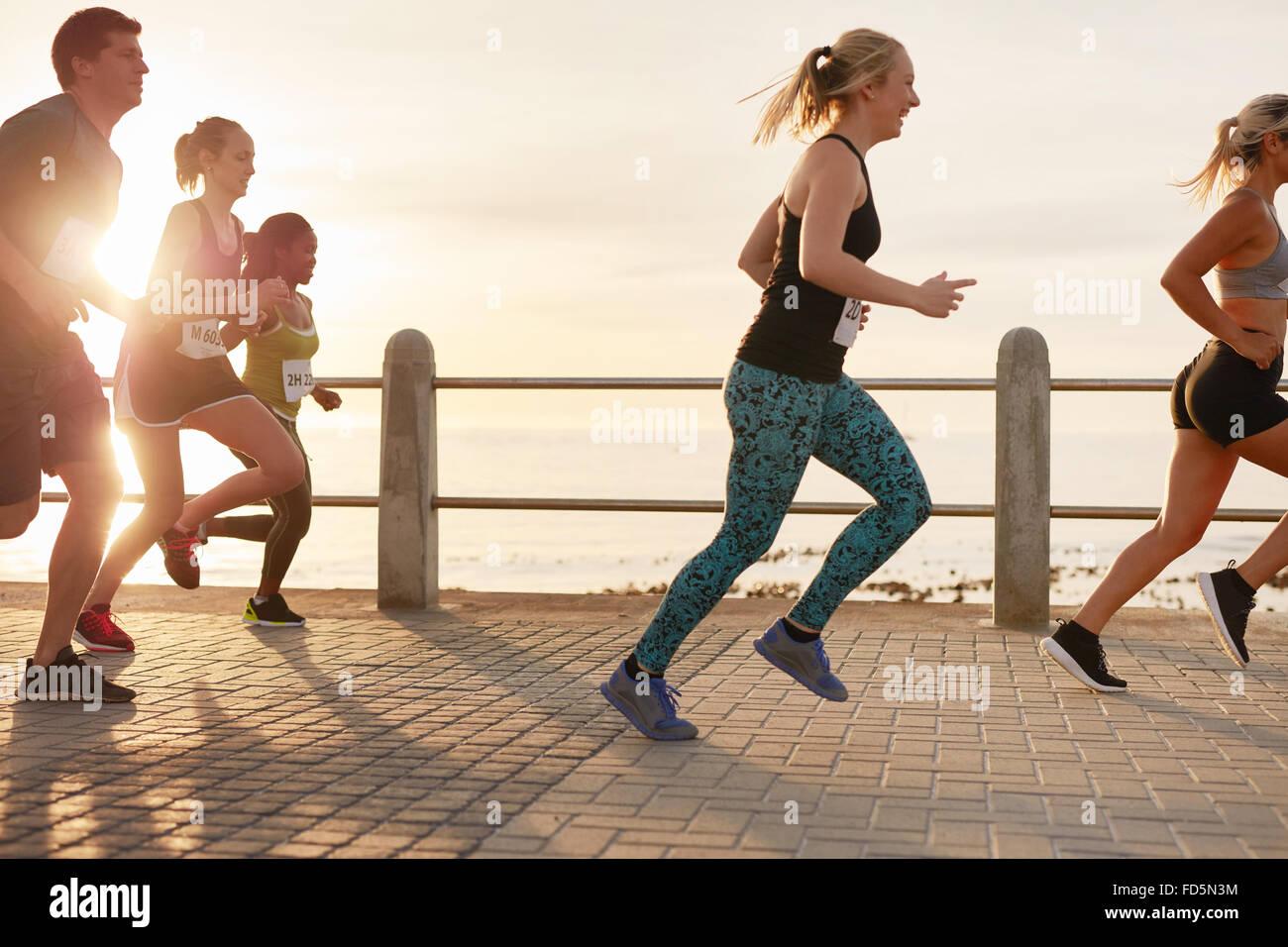Porträt des jungen Menschen direkt an Strandpromenade laufen. Männer und Frauen laufen Marathon unterwegs Stockbild