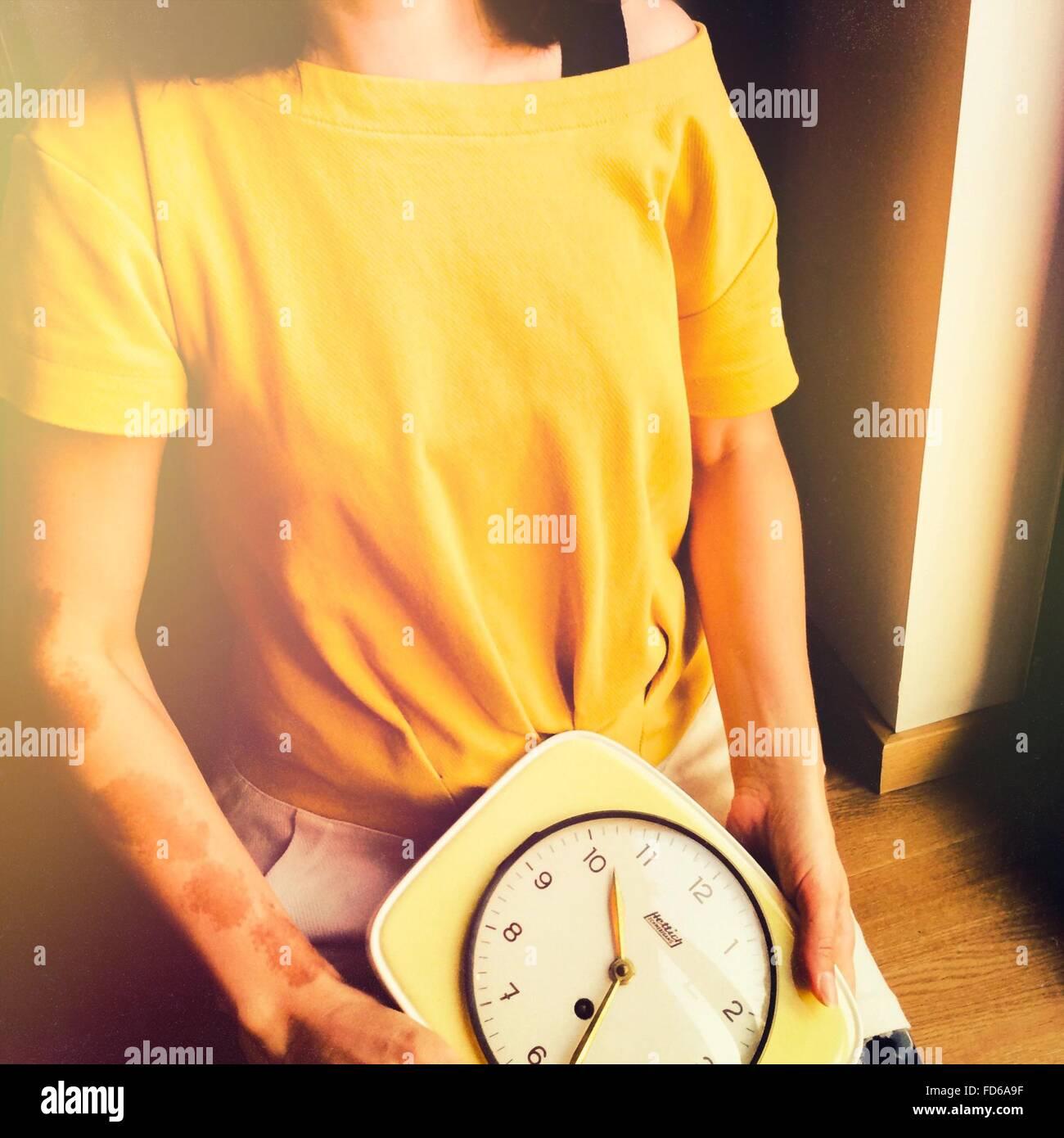 Frau hält eine Uhr Stockbild