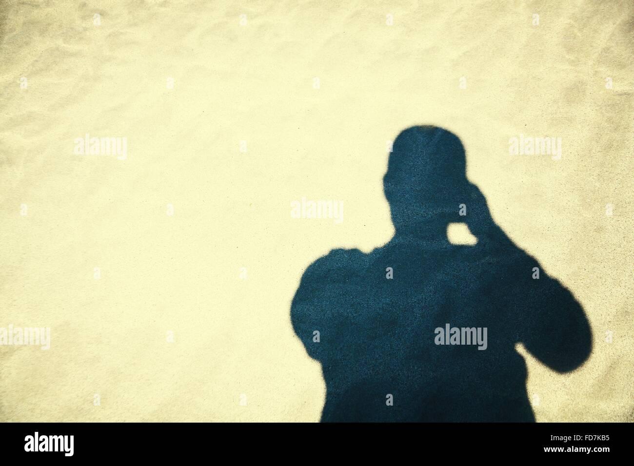 Schatten der Person über Sand Stockbild