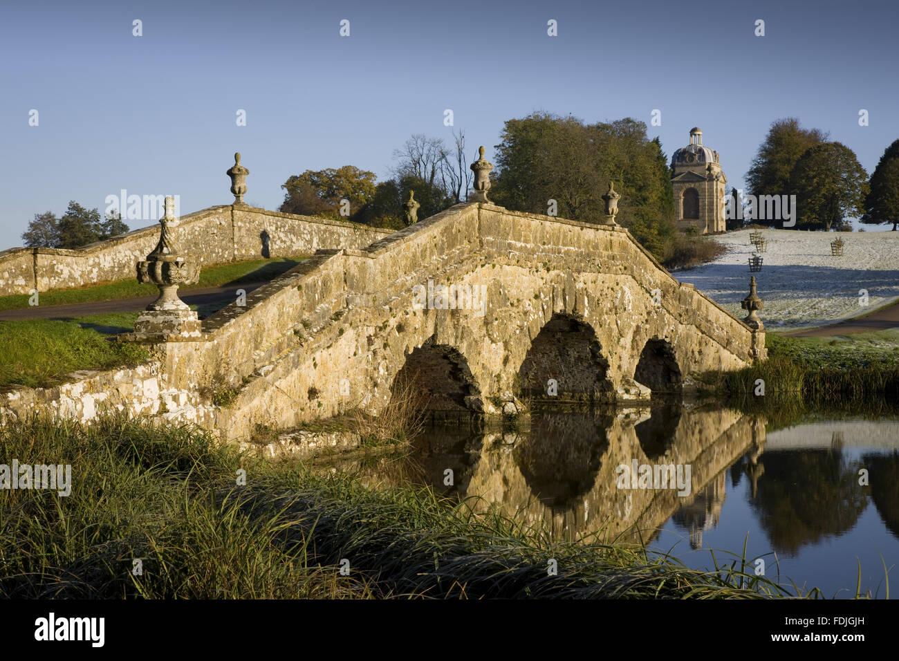 Die Oxford-Brücke mit Urnen und rustikales Mauerwerk an einem frostigen Tag in Stowe Landscape Gardens, Buckinghamshire. Stockbild