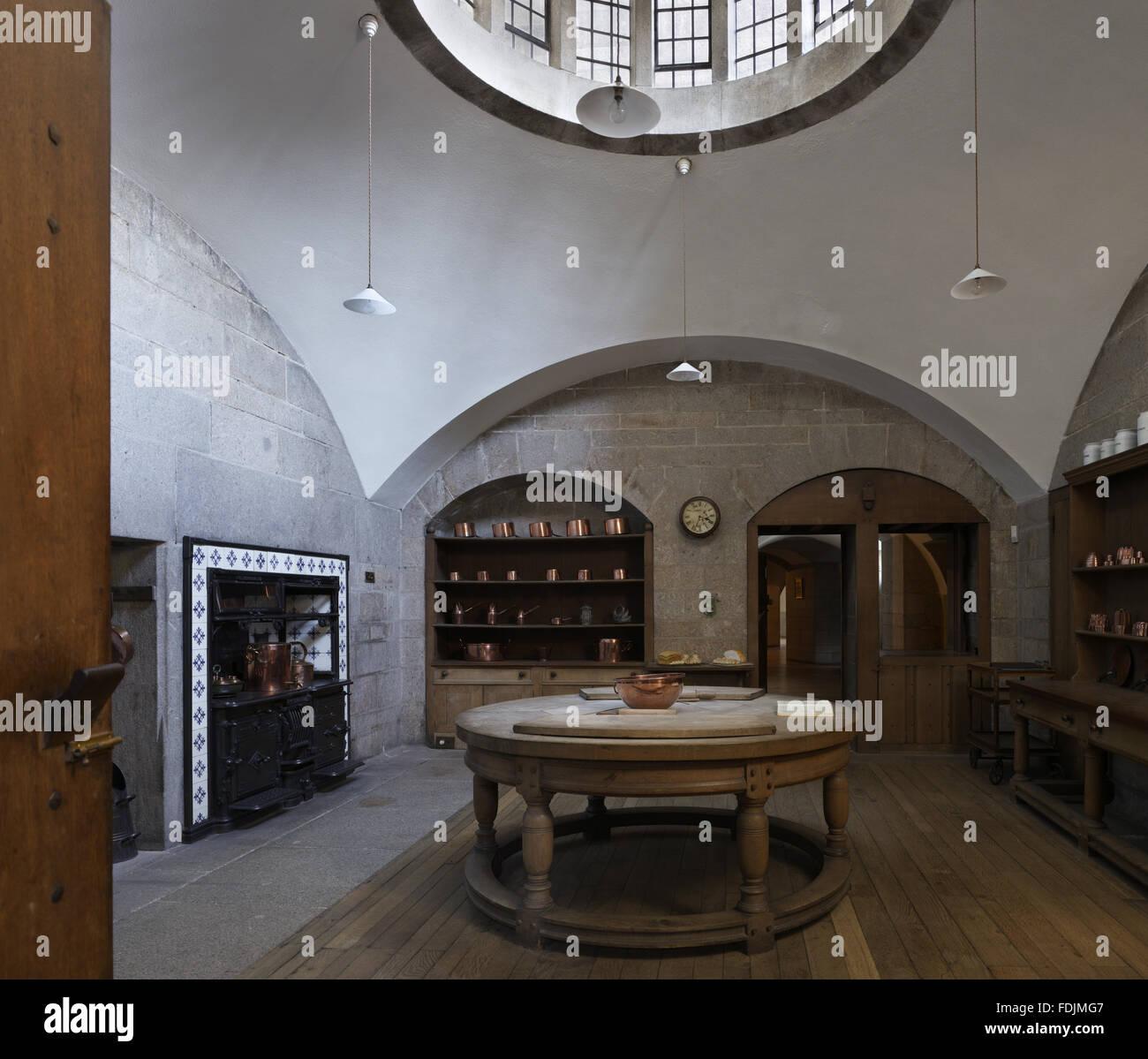 Die Küche im Castle Drogo, Devon, mit dem kreisförmigen Buchenholz Tisch von dem Architekten des Hauses, Stockbild