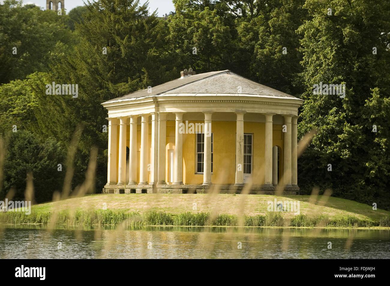 Der Musik-Tempel auf einer Insel im See im West Wycombe Park, Buckinghamshire. Der Tempel hat eine dorische Kolonnade Stockbild