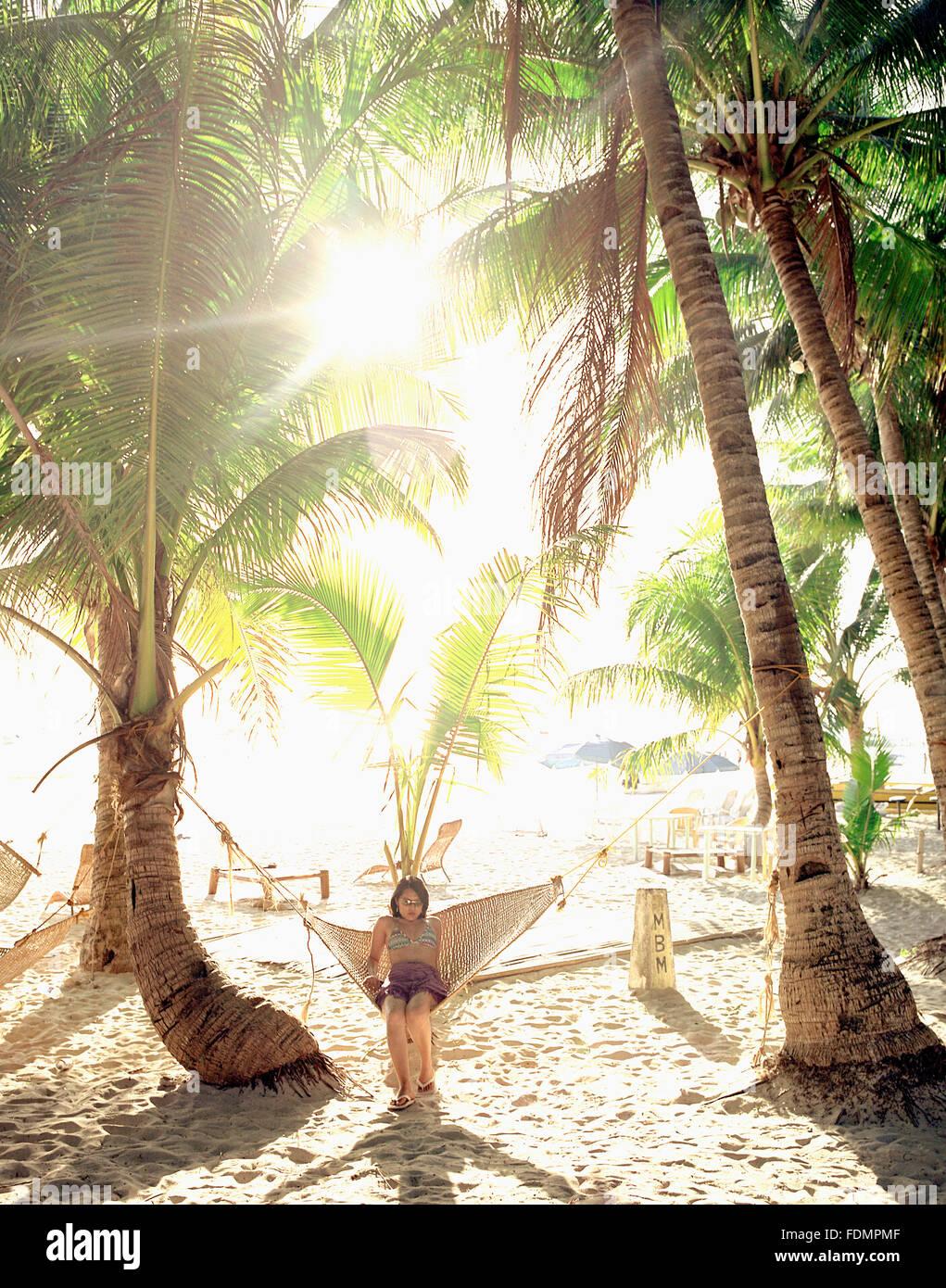 Eine junge Filipina Frau entspannt in der Hängematte bei Sonnenaufgang. Boracay, Philippinen. Stockbild