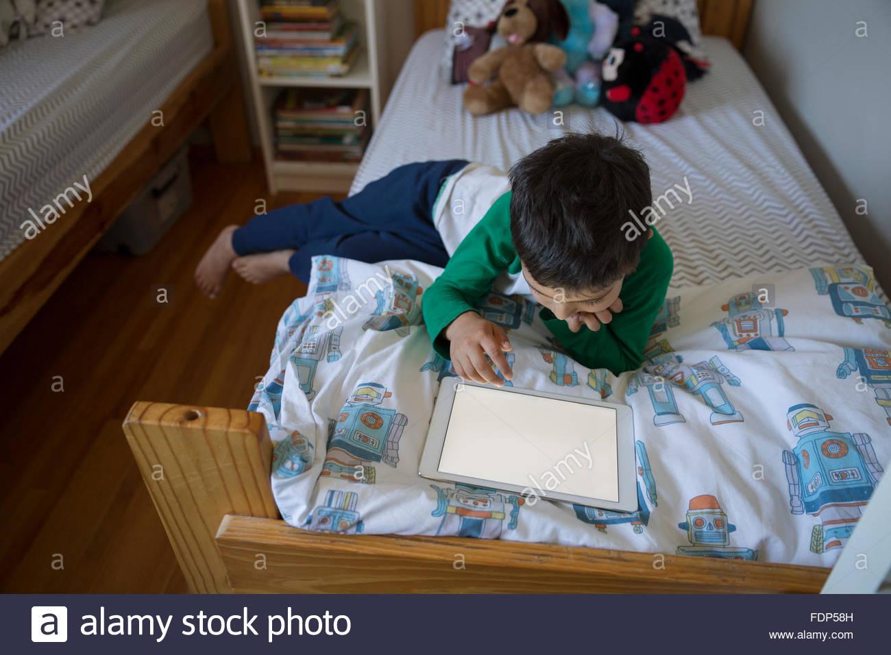 Junge zeichnen mit digital-Tablette auf Bett Stockbild