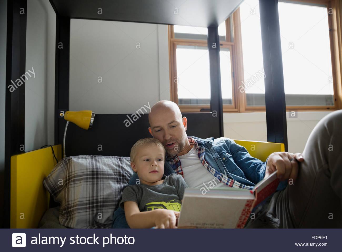 Vater und Sohn Lesebuch auf Bett Stockbild