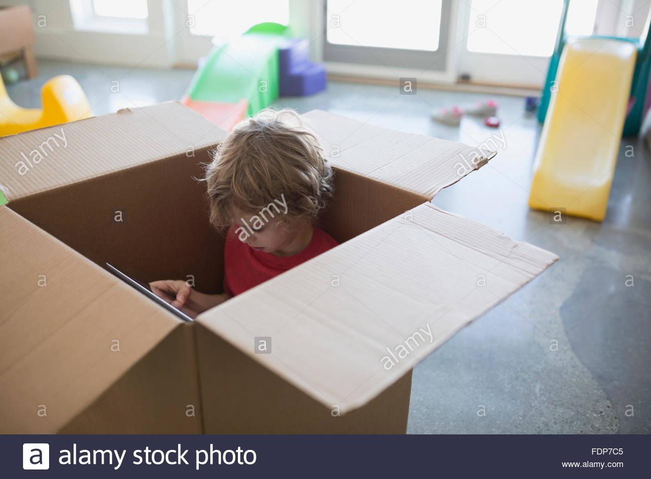 Junge mit digital-Tablette in Karton Stockbild