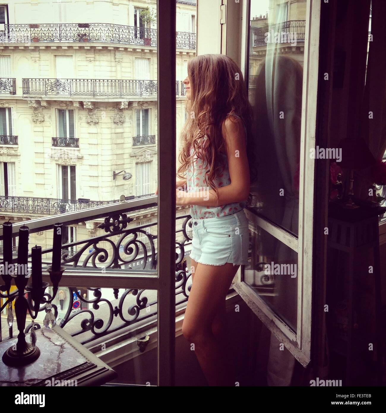 Seitenansicht der jungen Frau, die durch Fenster Stockbild
