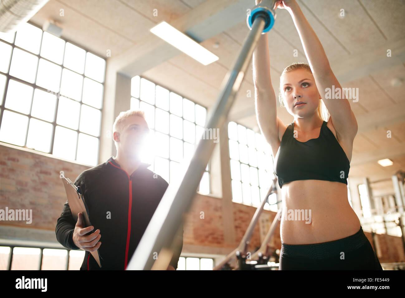 Weibchen mit ihrem persönlichen Trainer im Fitness-Studio trainieren. Junge Frau mit einer Langhantel in der Stockbild