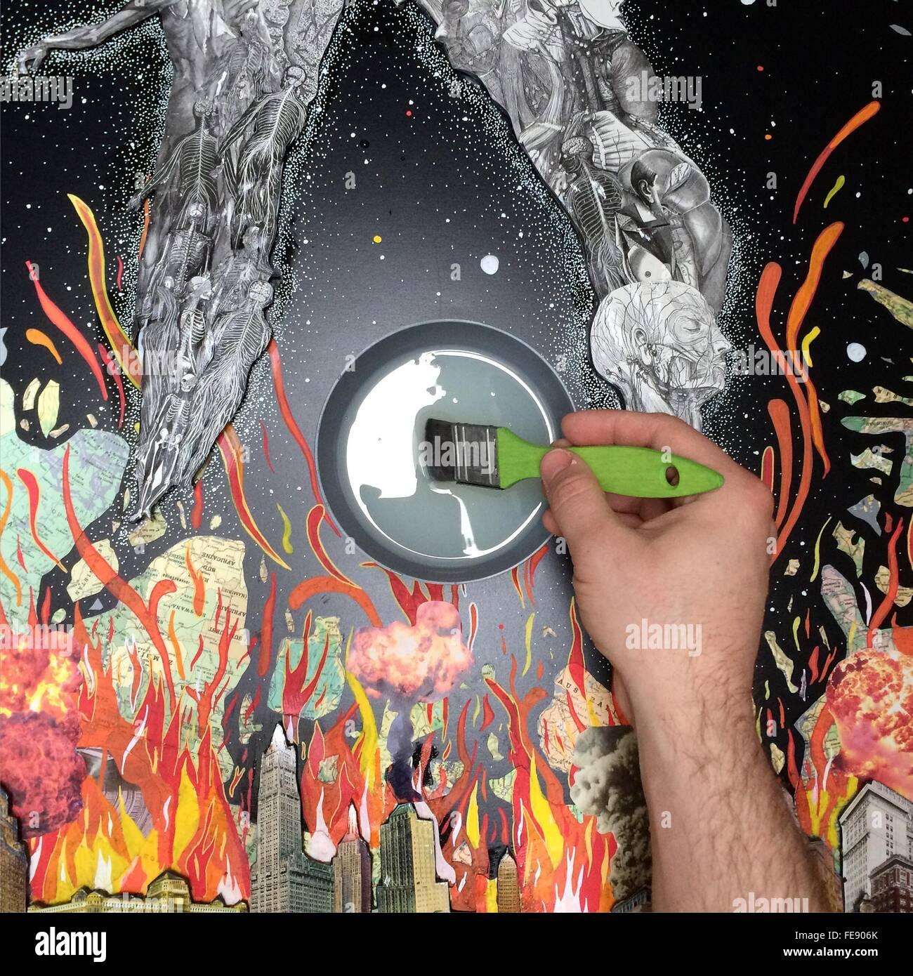 Mann hält Malerei Pinsel mit grauer Farbe auf die Malerei Stockbild