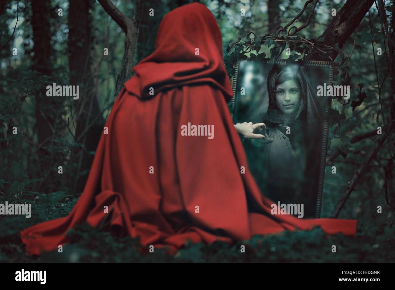 Geheimnisvolle rote Kapuze Frau vor einem magischen Spiegel. Dark fantasy Stockbild