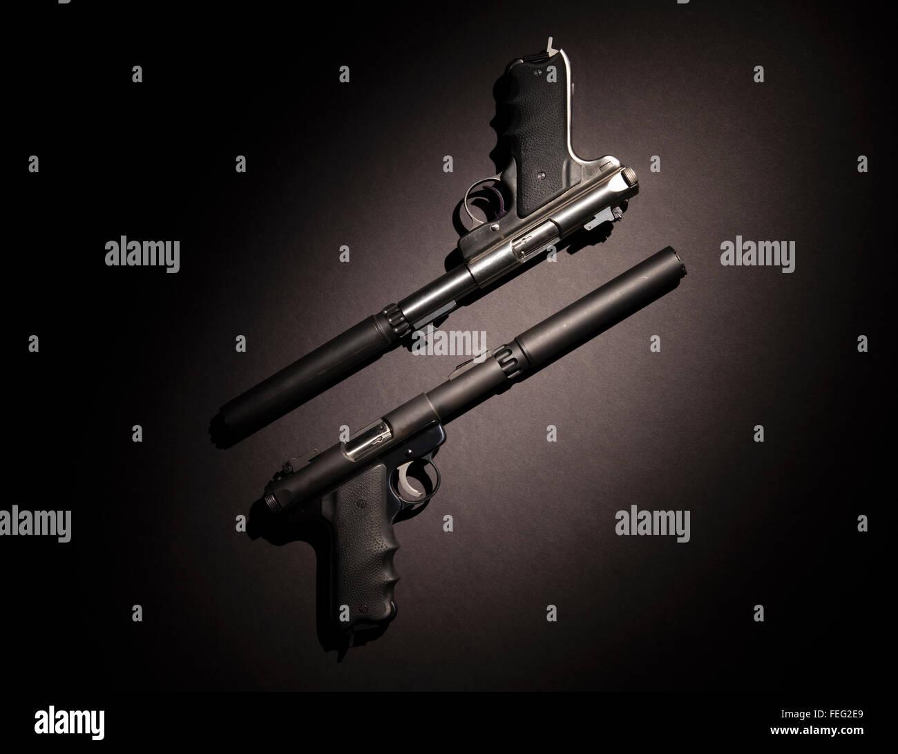 Zwei halbautomatische Pistolen mit Schalldämpfern auf schwarzem Hintergrund. Stockbild