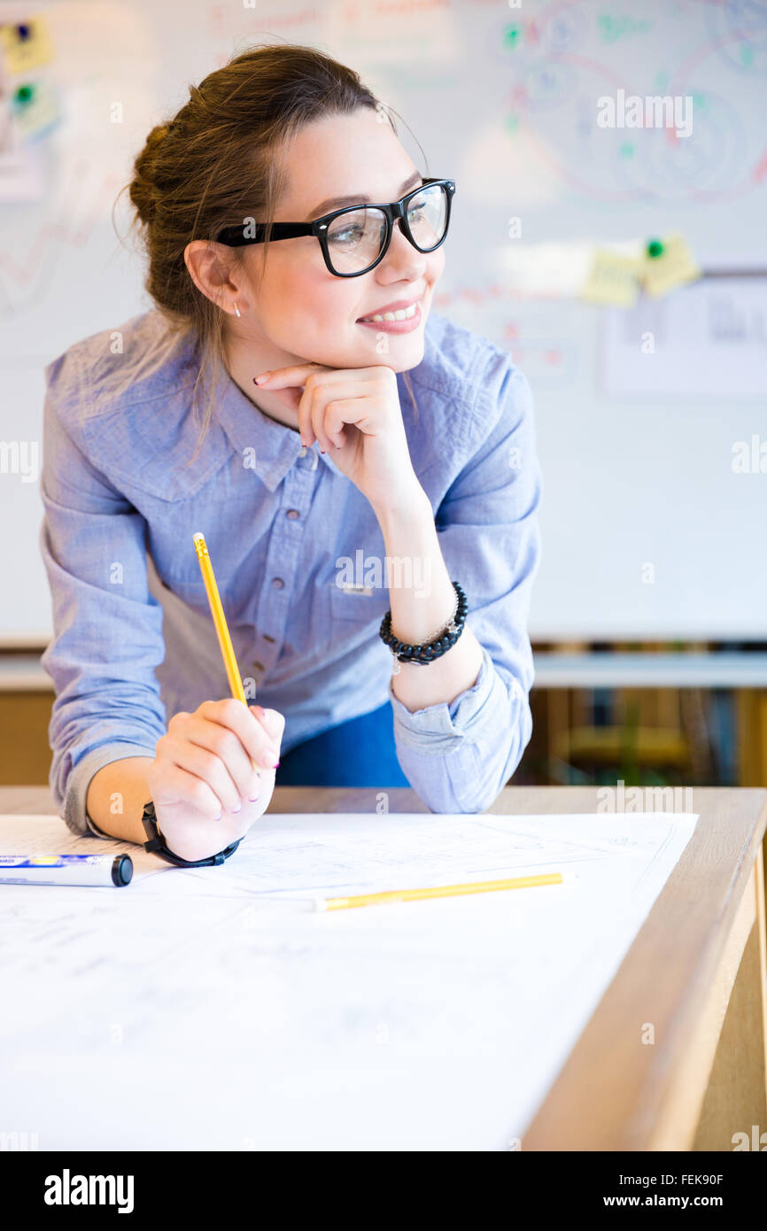 Schöne junge Geschäftsfrau inspiriert in Gläser, die im Büro arbeiten Stockbild