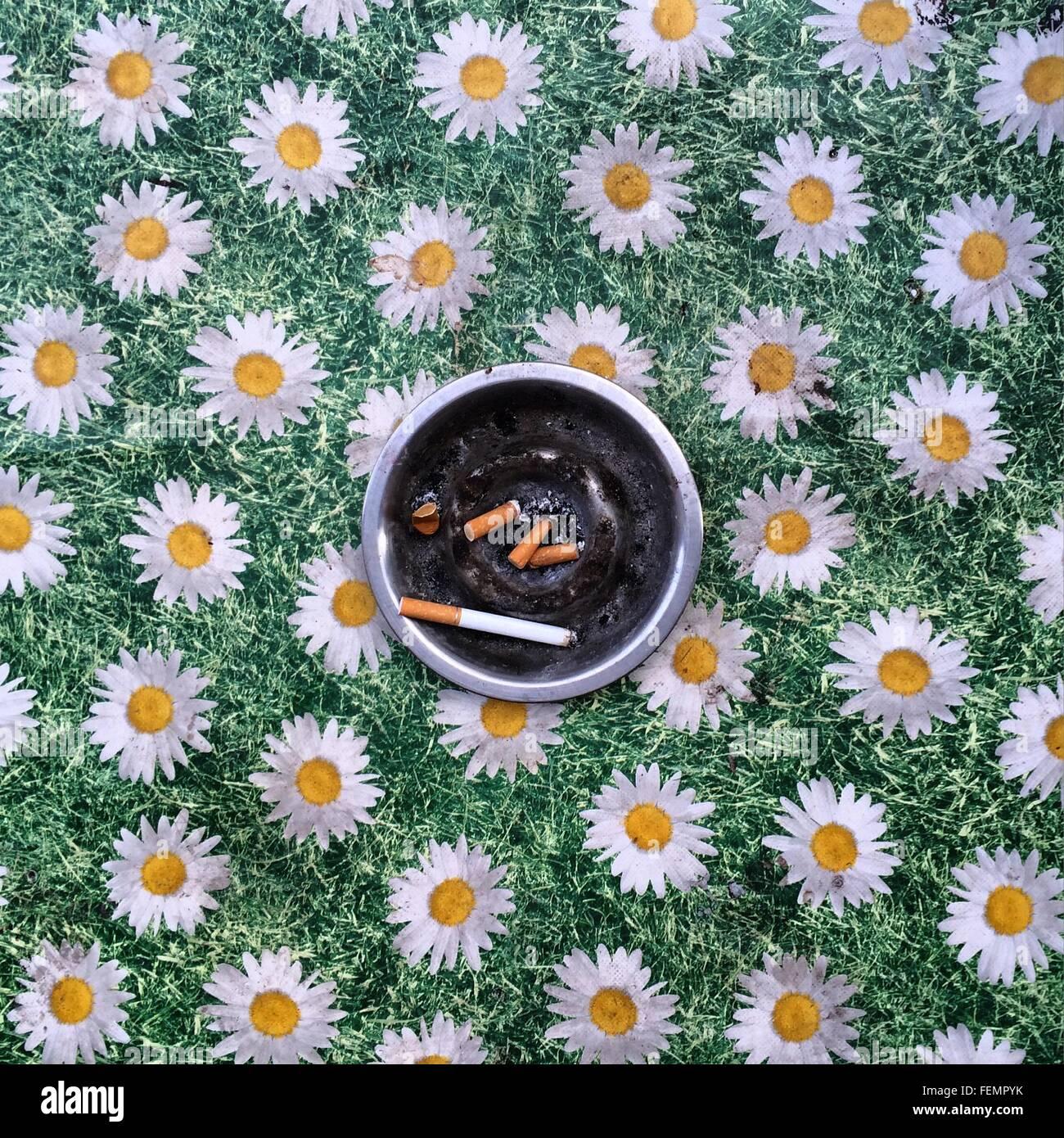 Aschenbecher auf Blumenmuster Tischdecke Stockbild
