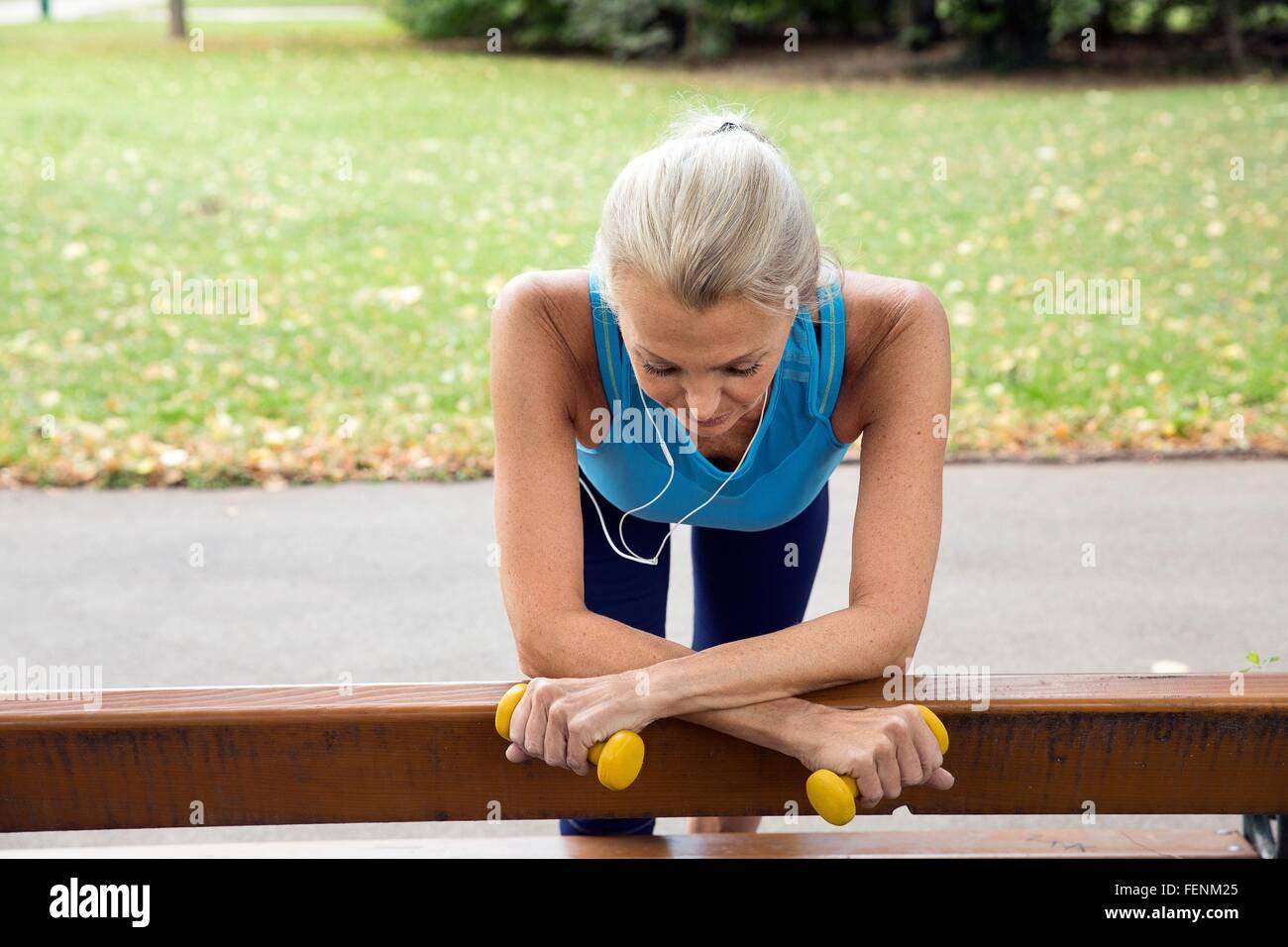 Reife Frau eine Pause auf der Parkbank beim training im park Stockbild