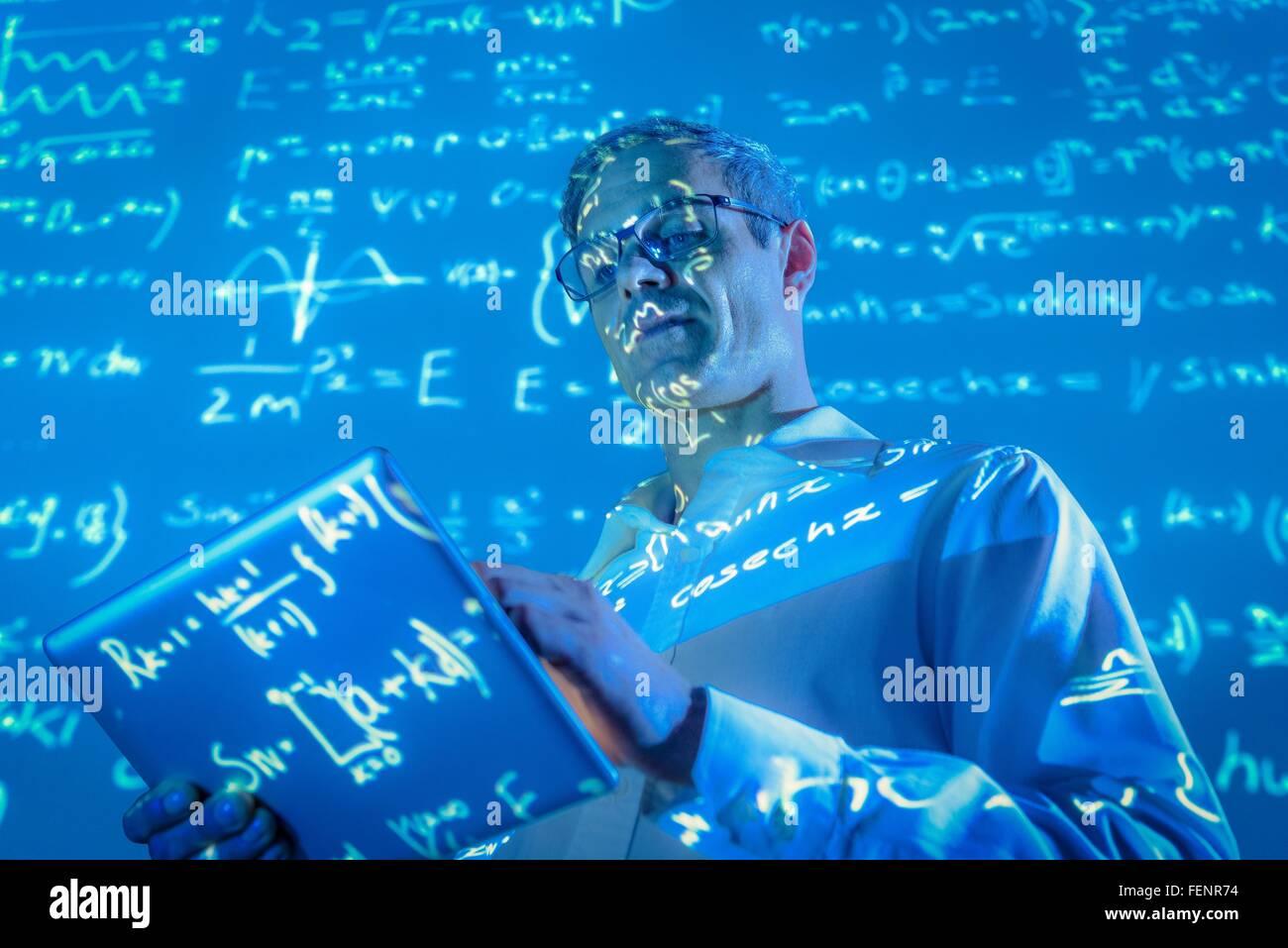 Wissenschaftler mit digital-Tablette und projizierte mathematische Daten Stockbild