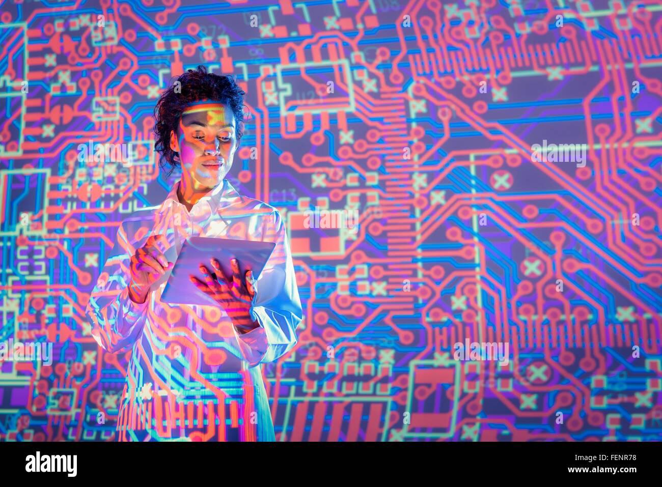 Wissenschaftlerin mit digital-Tablette mit grafischen elektronische Schaltung Projektion Stockbild