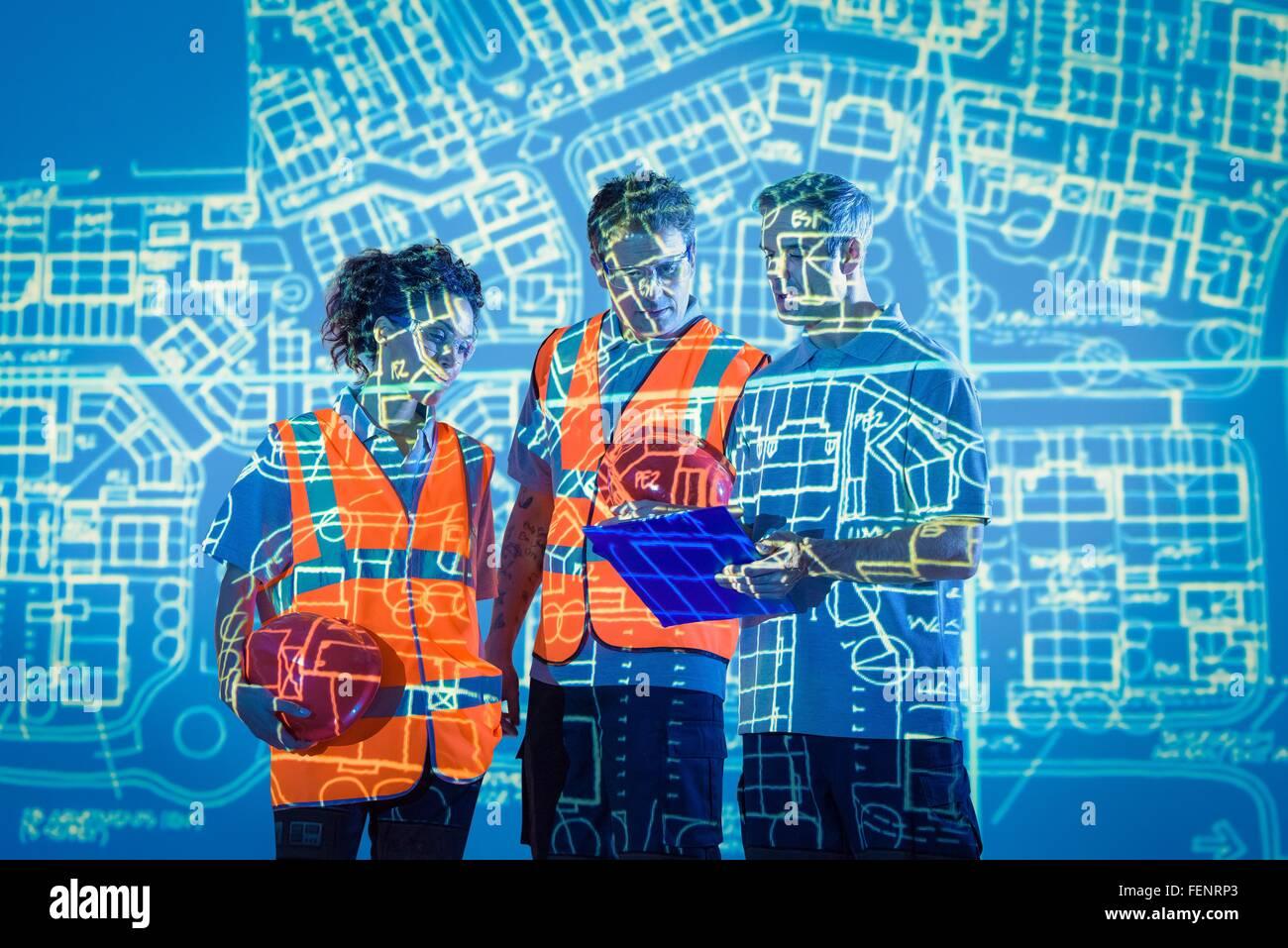 Ingenieure im Gespräch mit projizierten Pläne Stockbild