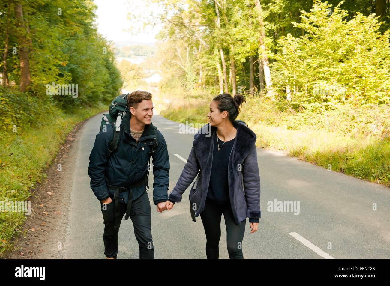 Junge Paar Holding wandern die Hände auf Landstraße Stockbild