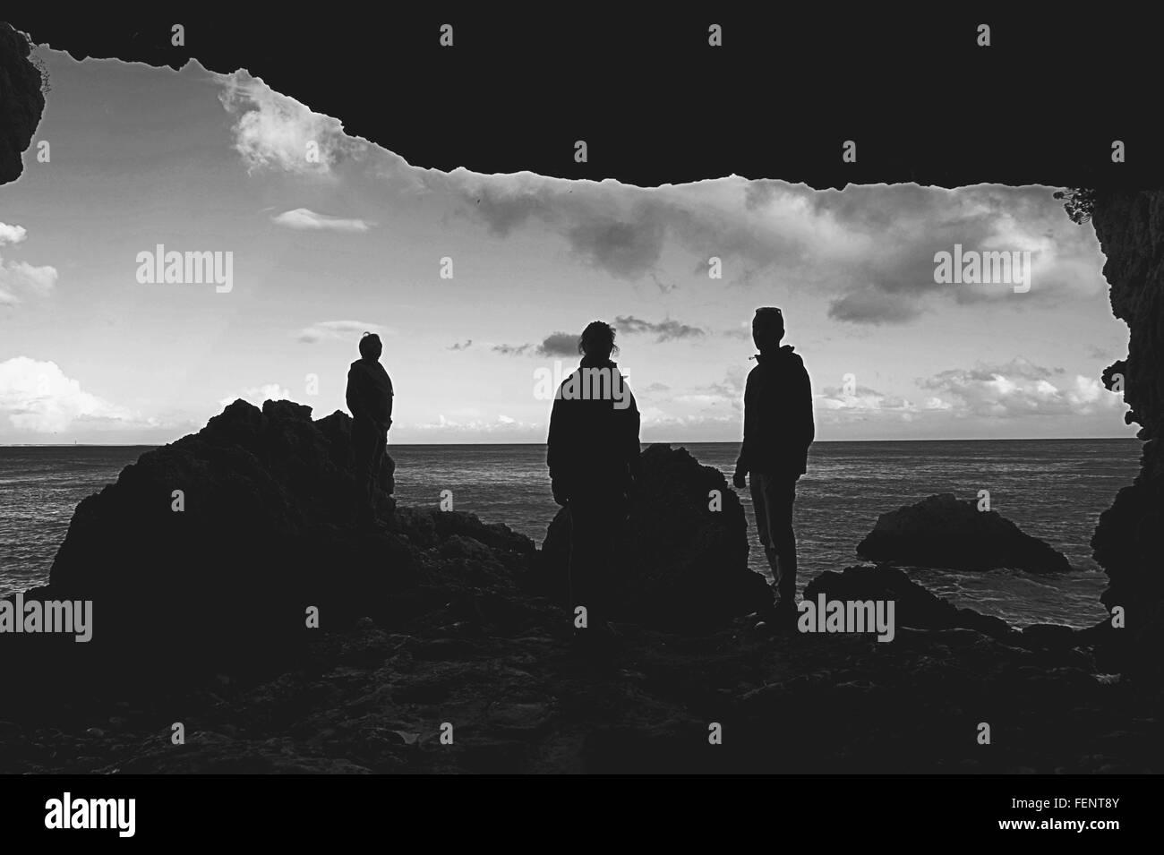Silhouette Menschen stehen am Strand von Felsen Stockbild