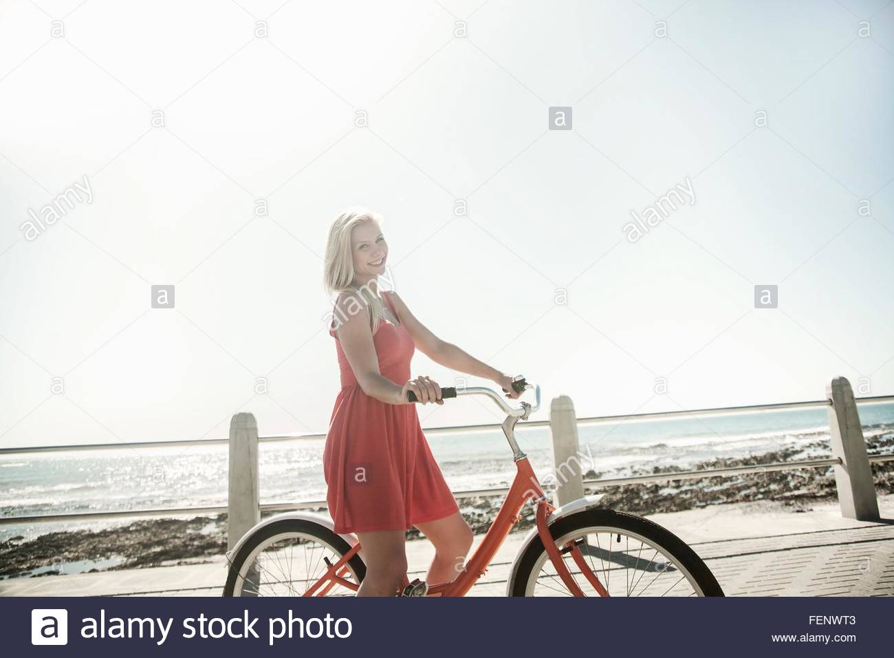 Junge Frau mit dem Fahrrad am Meer, Cape Town, Südafrika Stockbild