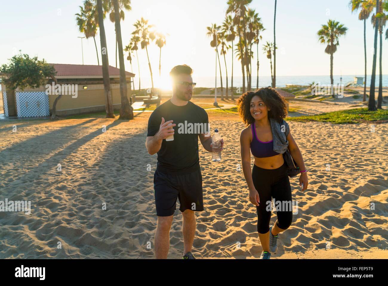 Paar tragen Sport Kleidung, Strand entlang spazieren, reden Stockbild