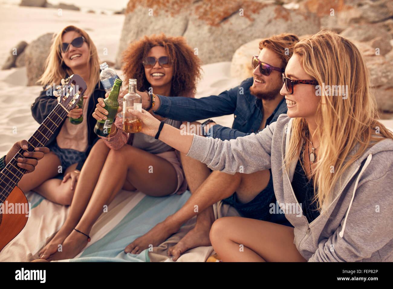 Junge Menschen sitzen zusammen am Strand und eine Party. Gruppe von Freunden jubelt mit Bier am Strand. Stockbild
