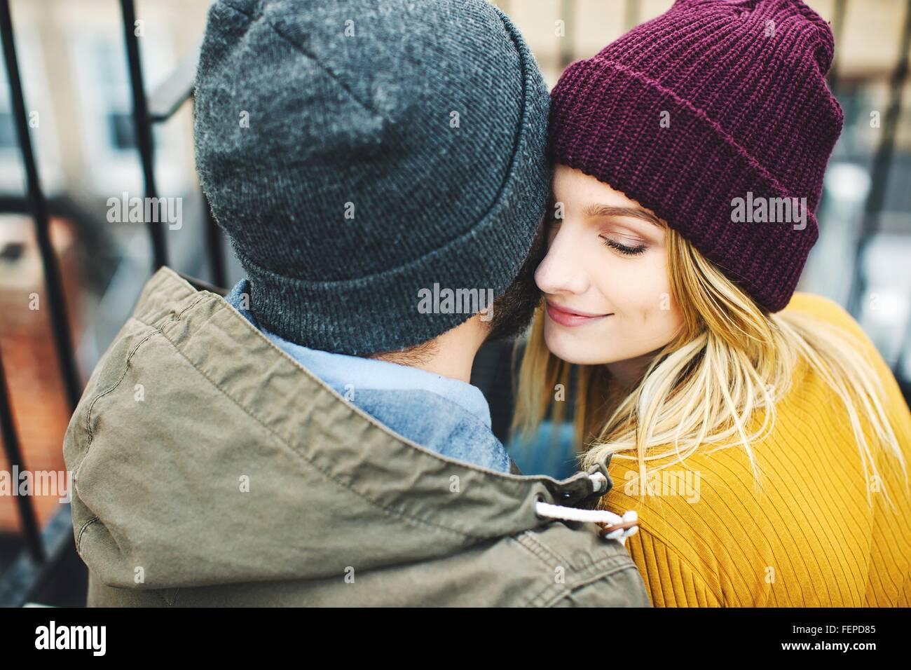 Romantische junges Paar tragen Strickmützen sitzt auf der Treppe Stockbild