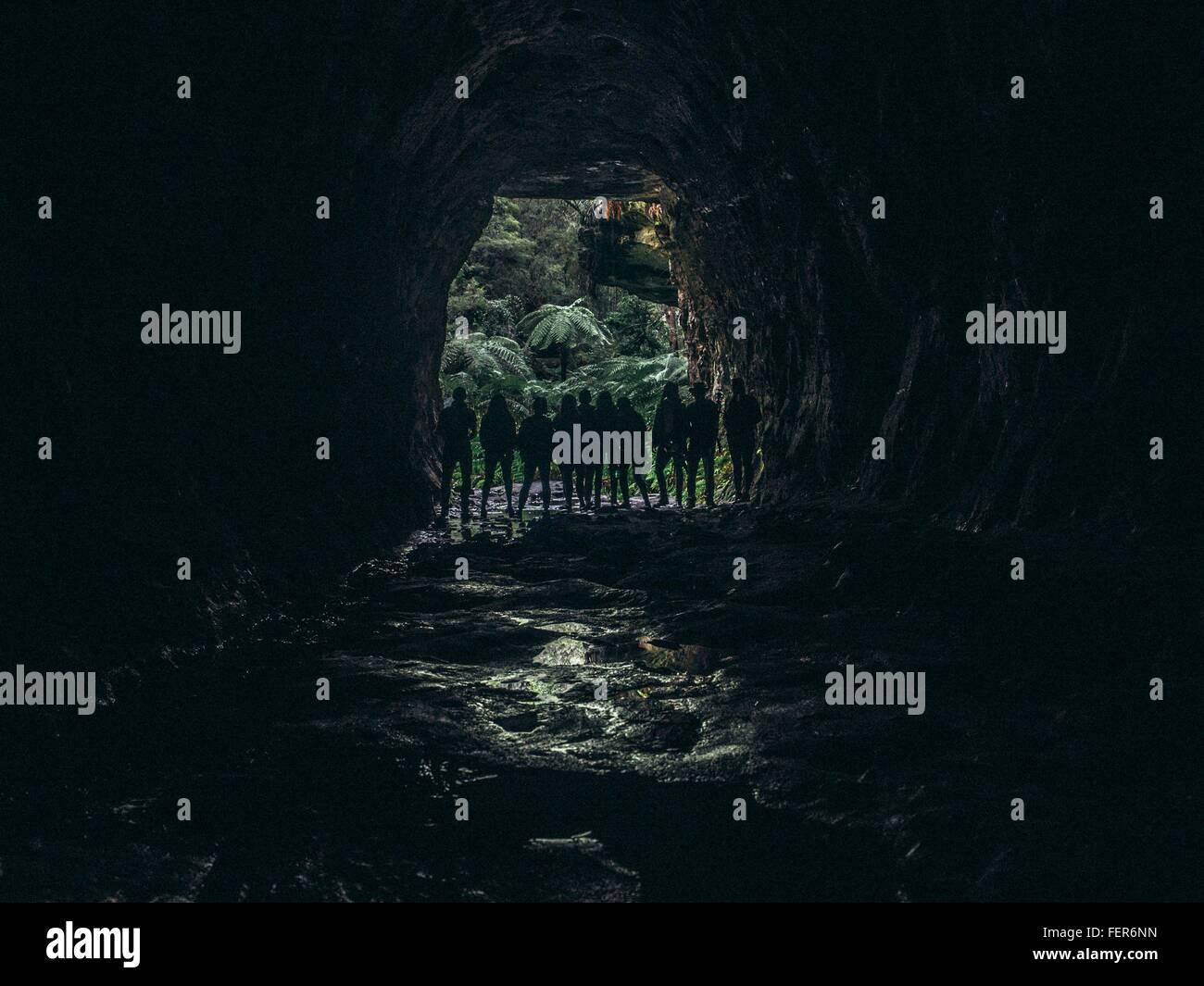 Silhouette des Menschen stehen am Eingang der Höhle Stockbild