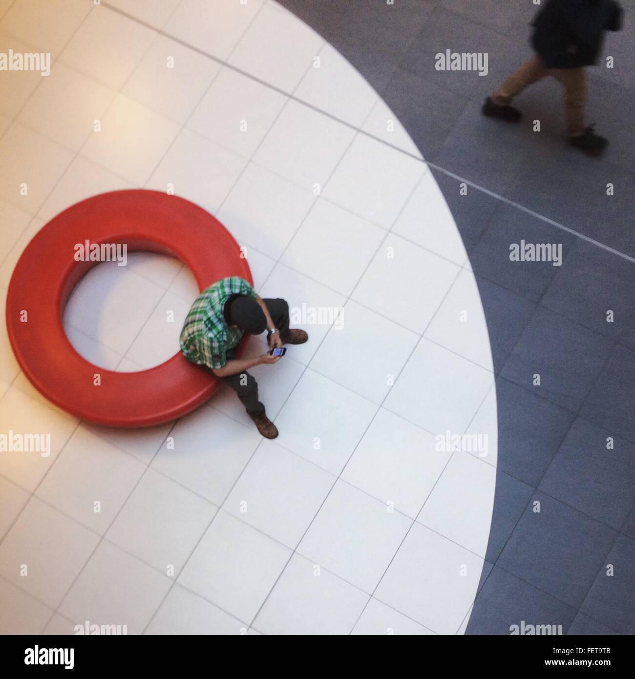 High Angle View Of Mann mit Handy In Lobby Stockbild