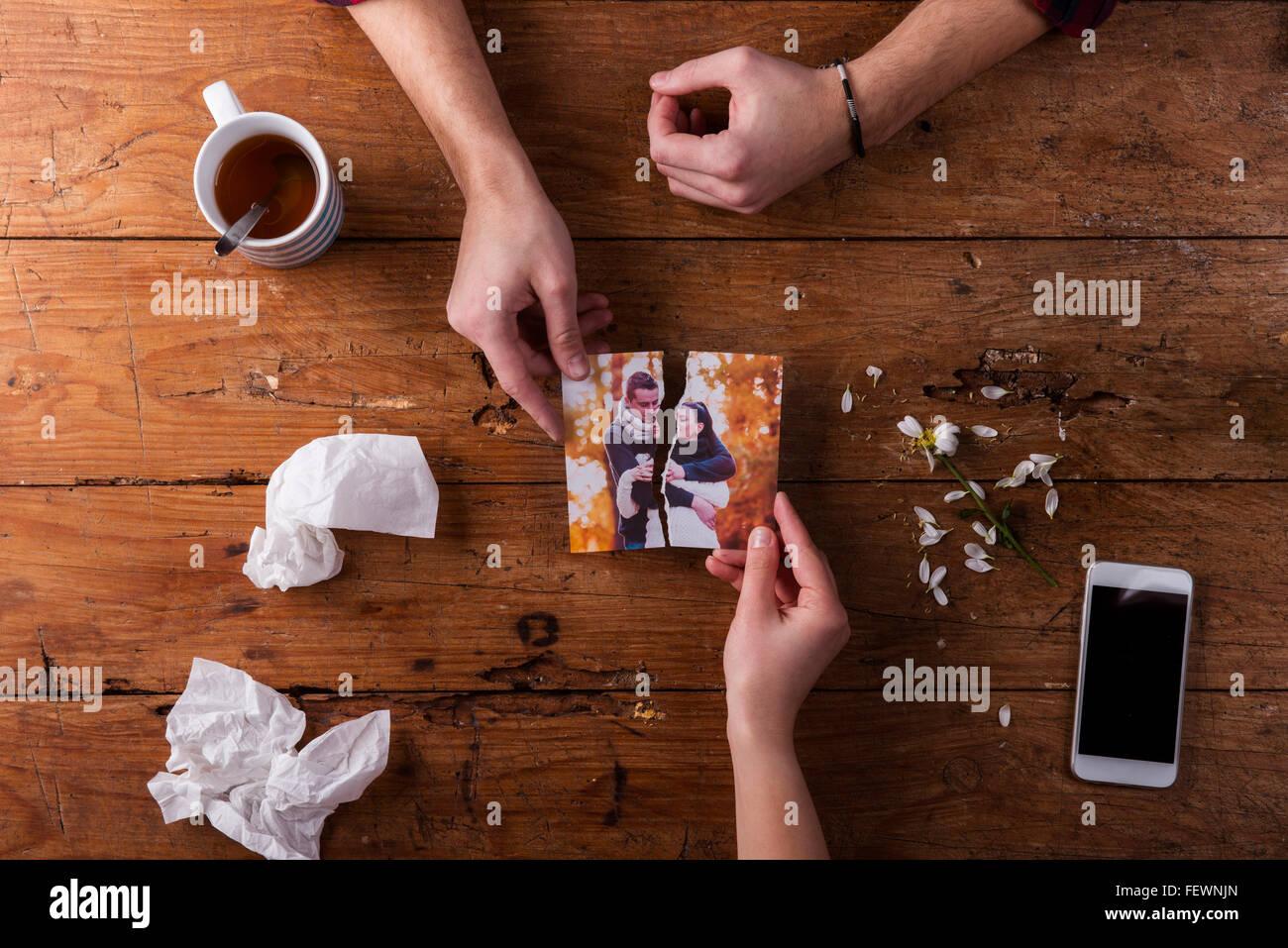 Sad mans, Womans Hände halten zerrissenes Bild von romantisch zu zweit. Stockbild