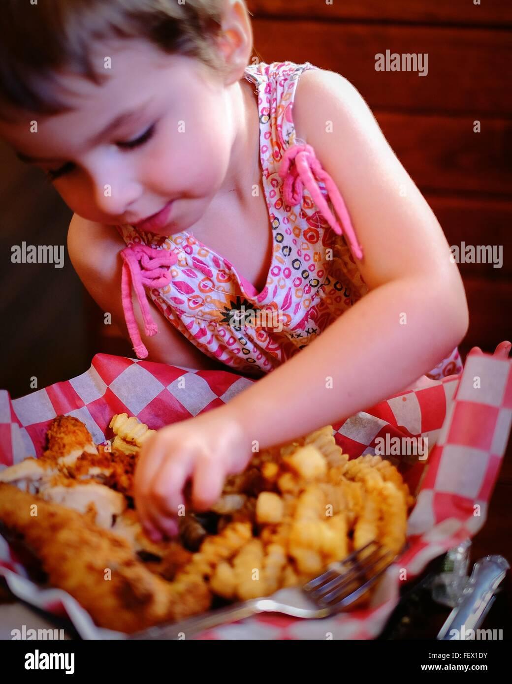 Niedliche Mädchen mit Chicken Fingers im Restaurant Stockbild