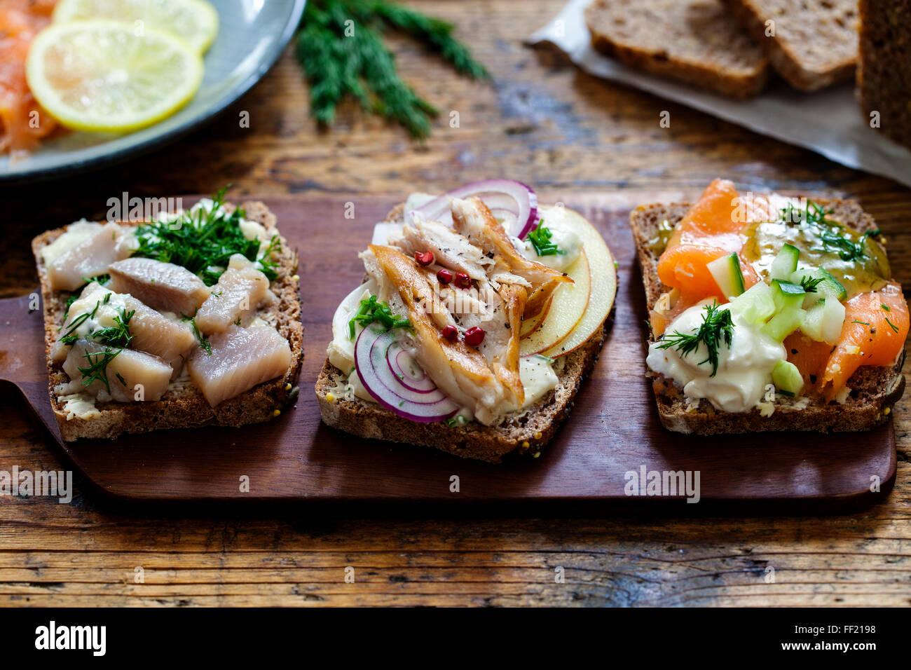 Skandinavische Sandwiches mit geräucherter Makrele, Hering und Lachs Stockbild