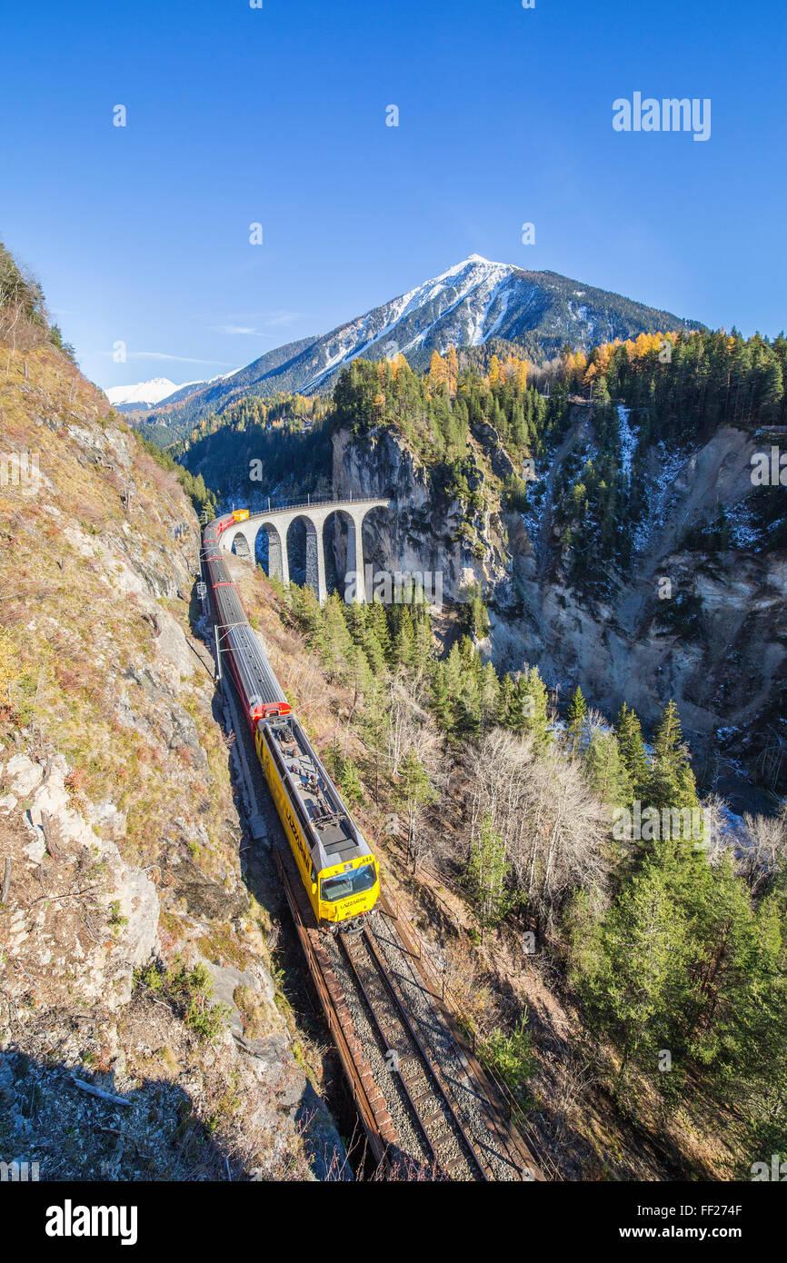 Bernina Express führt über das Landwasser Viadukt umgeben von bunten Wäldern, Kanton Graubünden, Stockbild