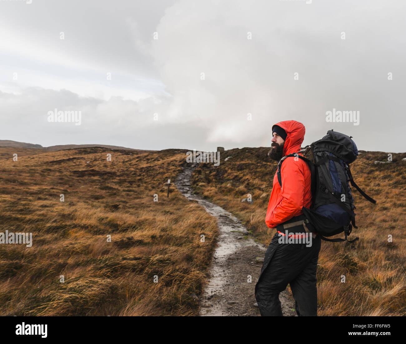 Ein Mann im Winterkleidung, Regenjacke und Rucksack in der offenen Landschaft durch einen Pfad. Stockbild