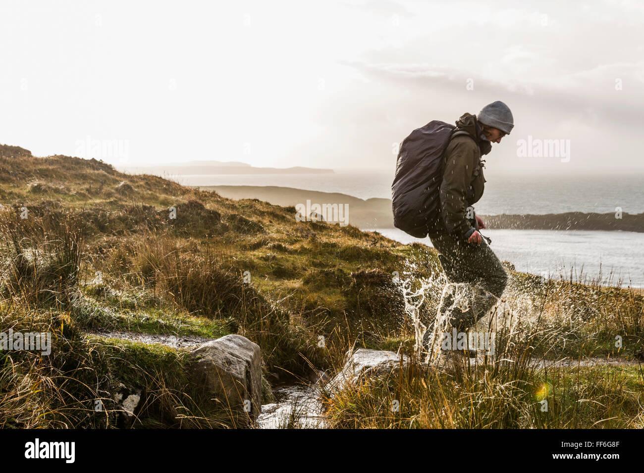 Ein Mann mit einem Rucksack und Winter Kleidung springen über einen kleinen Bach in eine exponierte Offenland. Stockbild