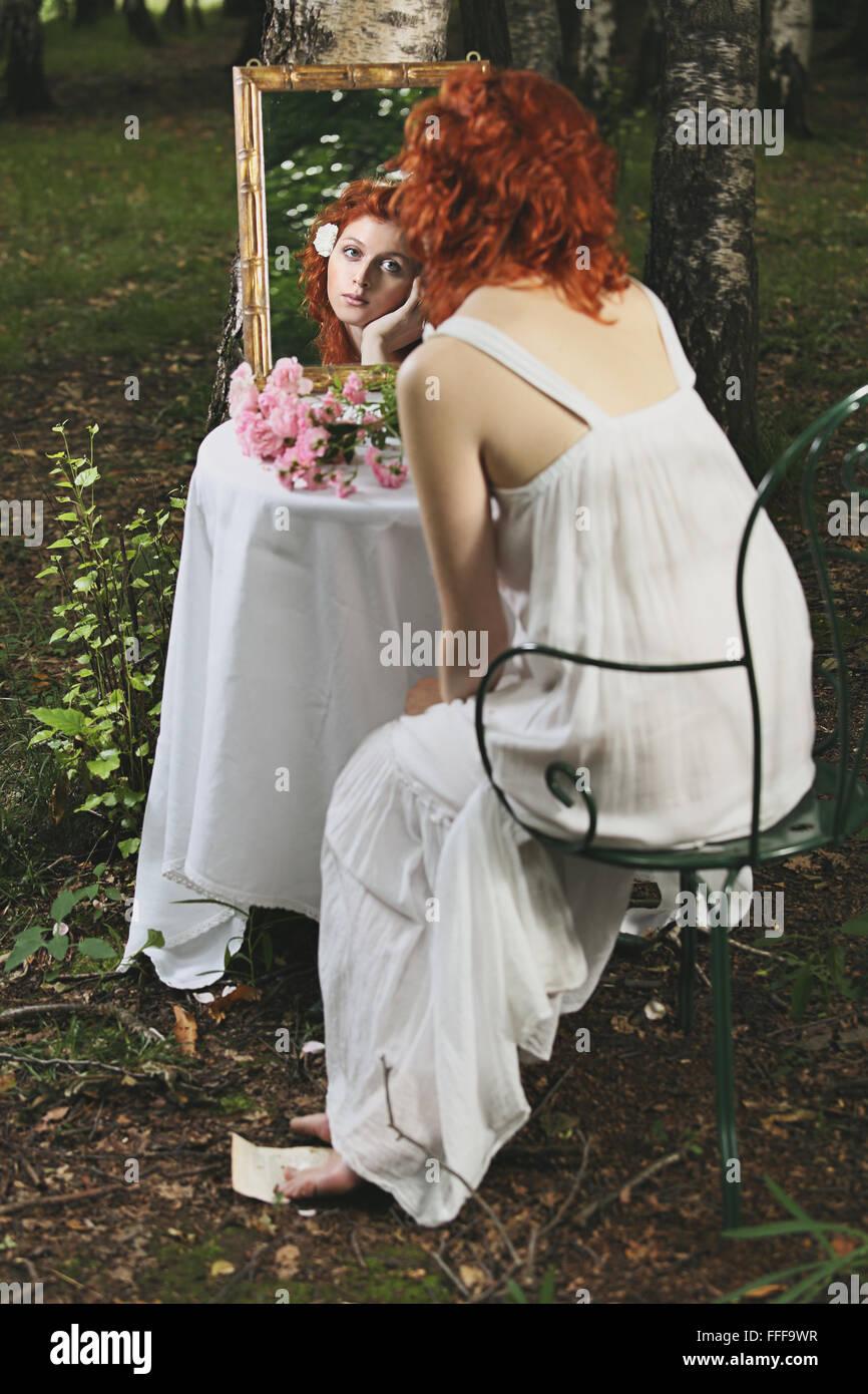 Rote Haare Frau Spiegelbild in einem Wald. Surreal und vintage Stockbild