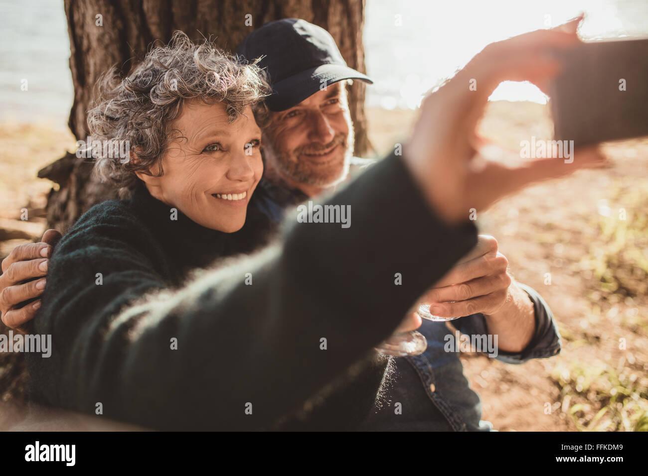 Gerne älteres Paar an ihre Selbstporträt mit ihrem Handy am camping Tag. Mann und Frau sitzen zusammen Stockbild