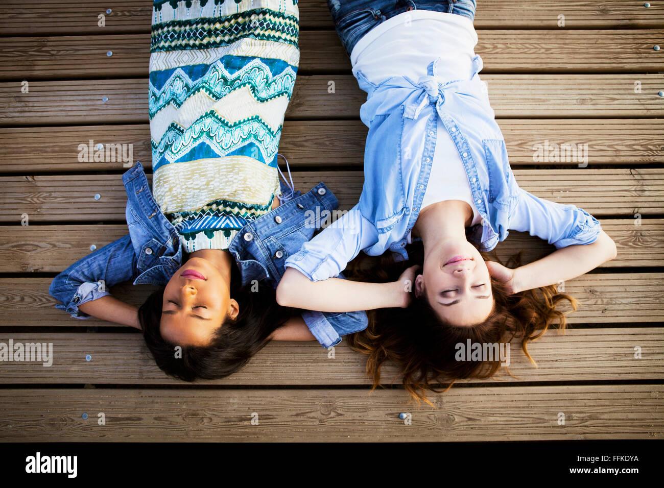 Zwei Frauen auf Rücken liegend mit Augen geschlossen Stockbild