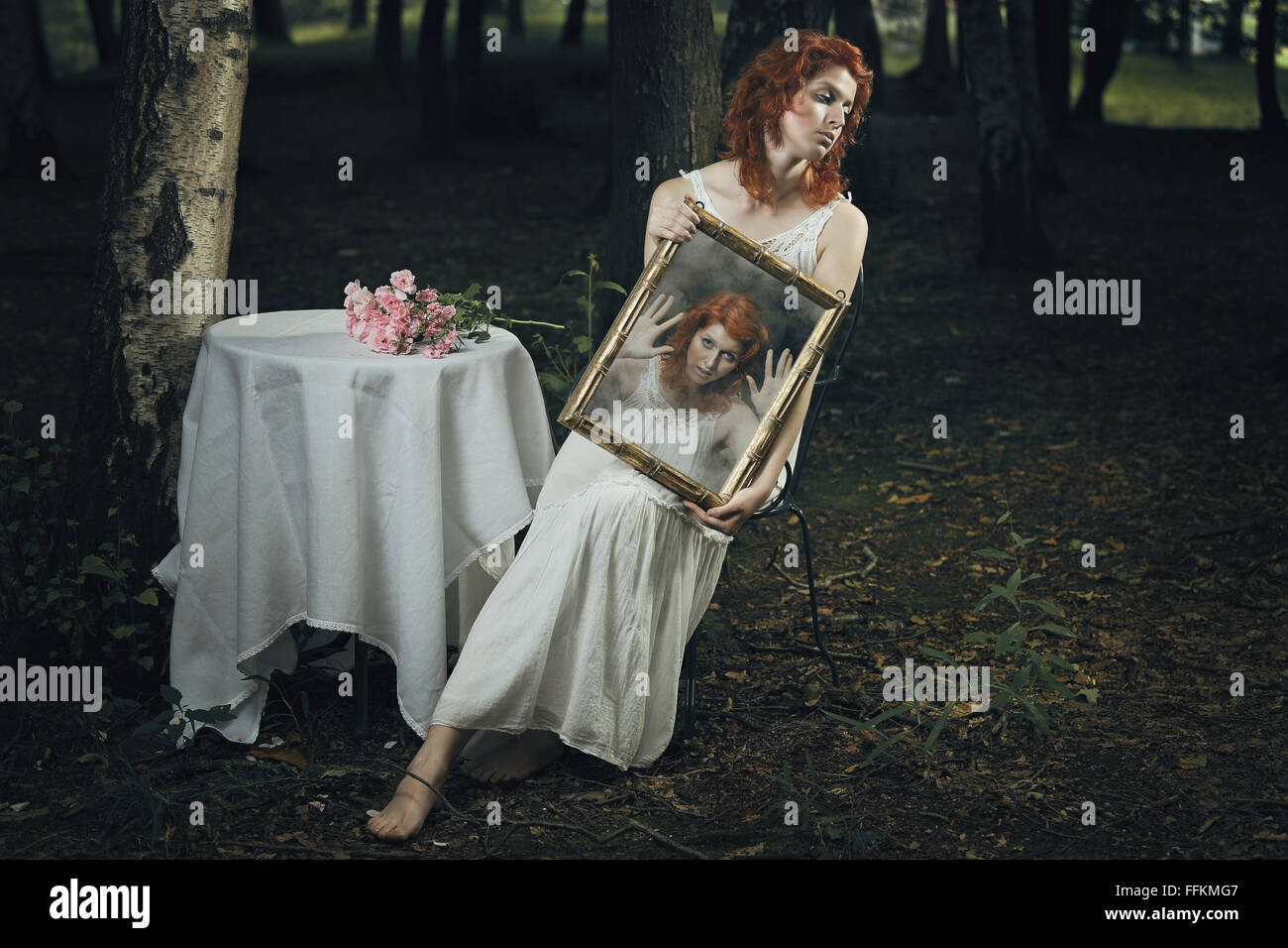 Seele einer Frau gefangen in einem Spiegel in einem seltsamen Wald. Dunkel und surreal Stockbild